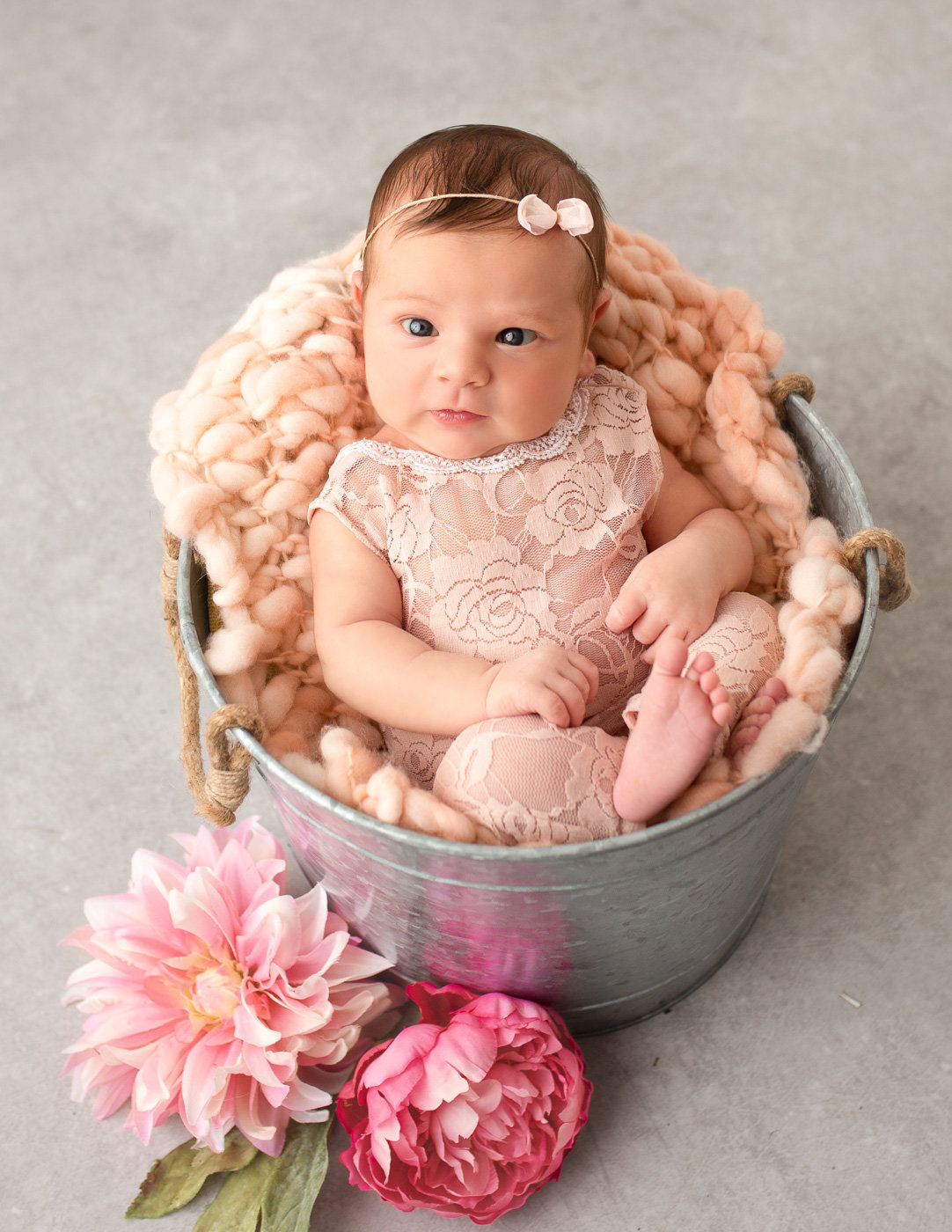 Awake newborn girl posed in a bucket in our in home studio in Rochester NY.