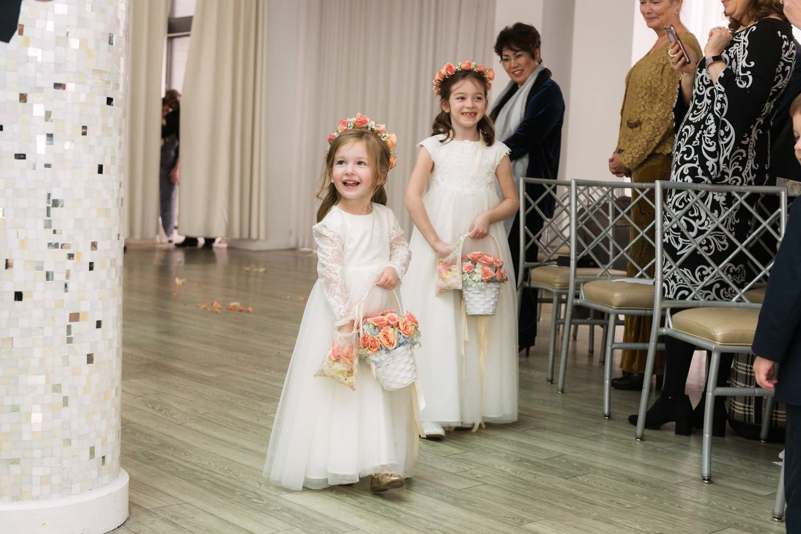 Flower girls walking down the aisle at  Allegria Hotel