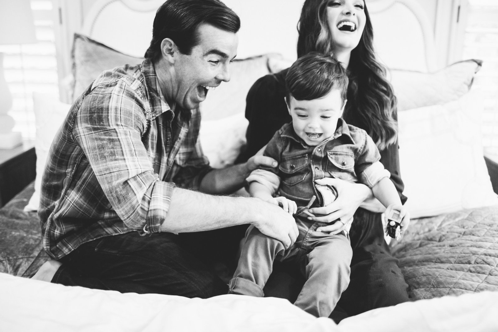 Mom and dad playing with son at home in bed