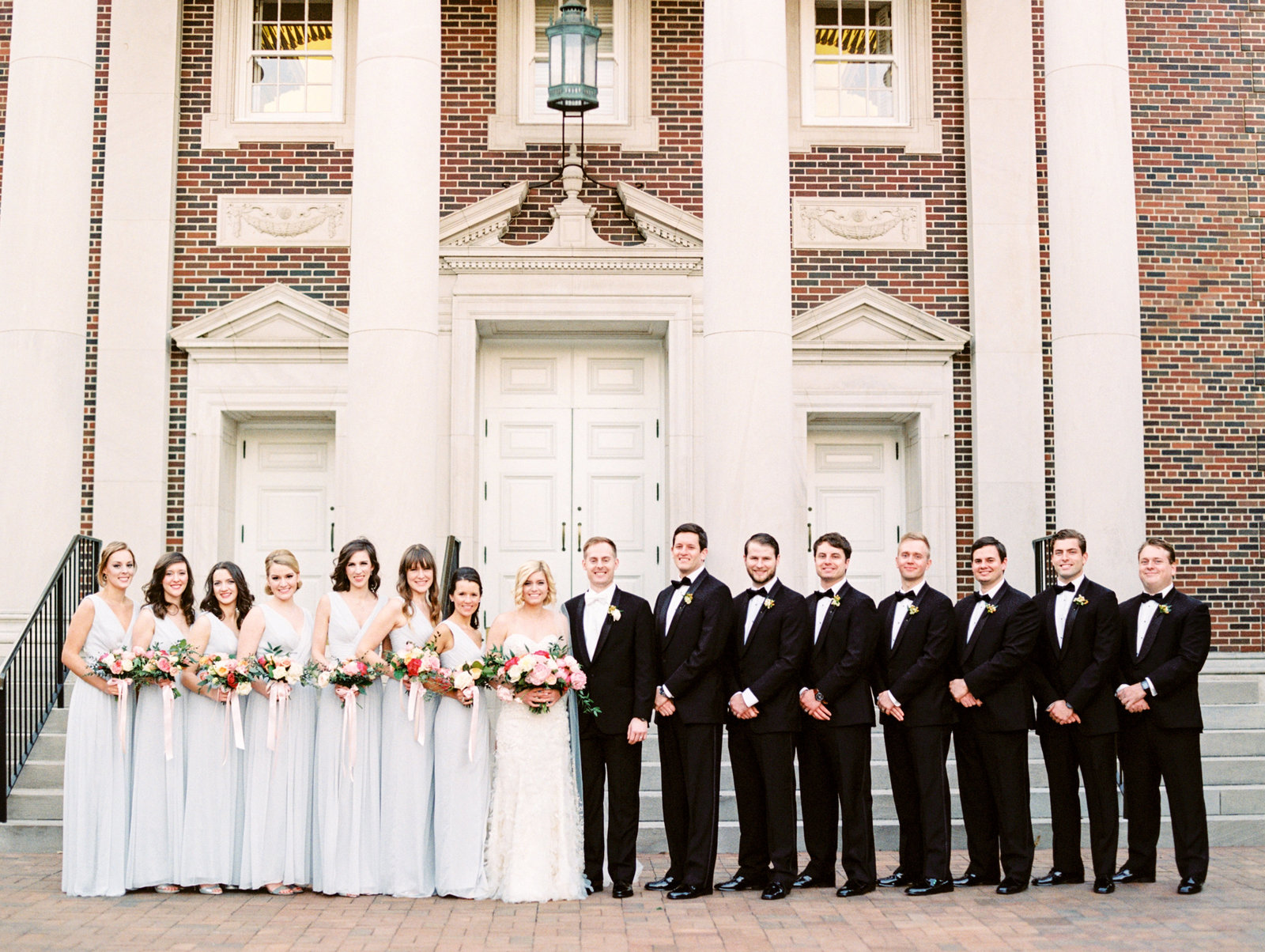 full wedding party posing in front of perkins chapel in dallas texas