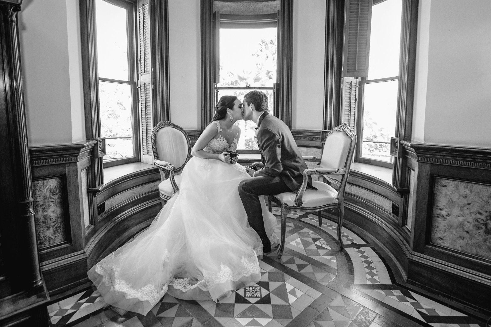 bride and groom share a coffee and  a kiss in the library of the newhall mansion