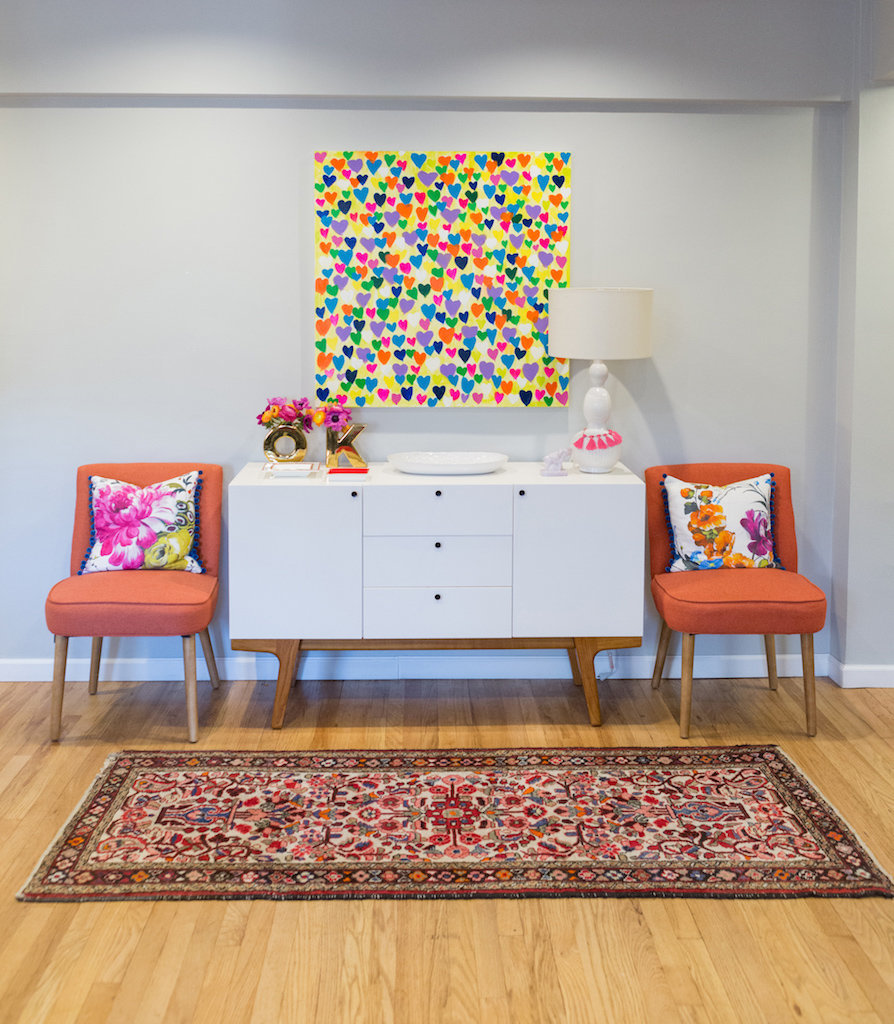 A modern white side table, colorful heart painting, and orange chairs.