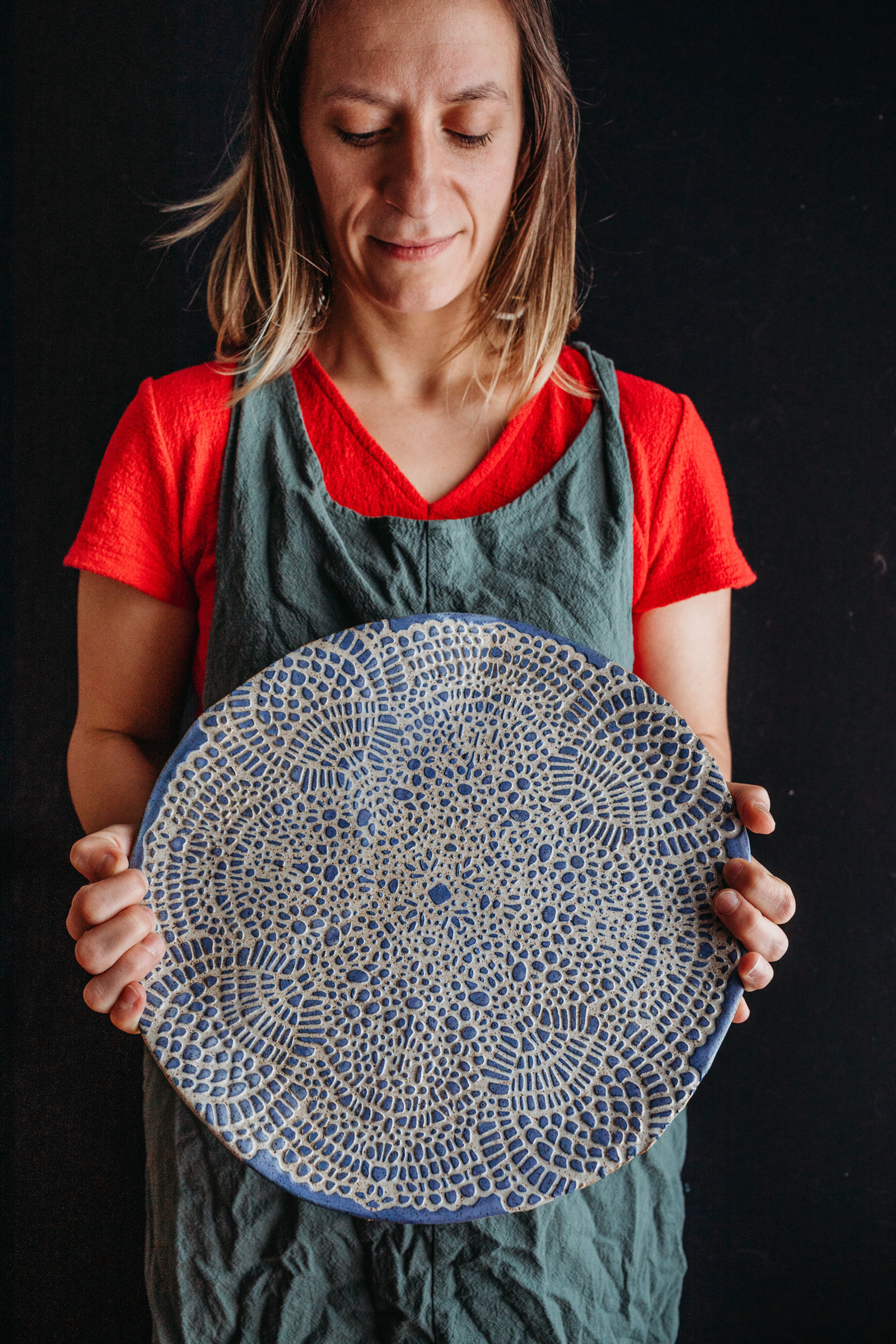 woman holds hand designed clay platter