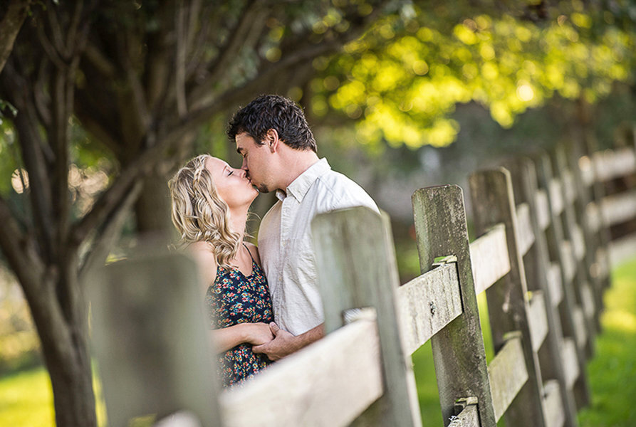 Engaged couple kissing by fence