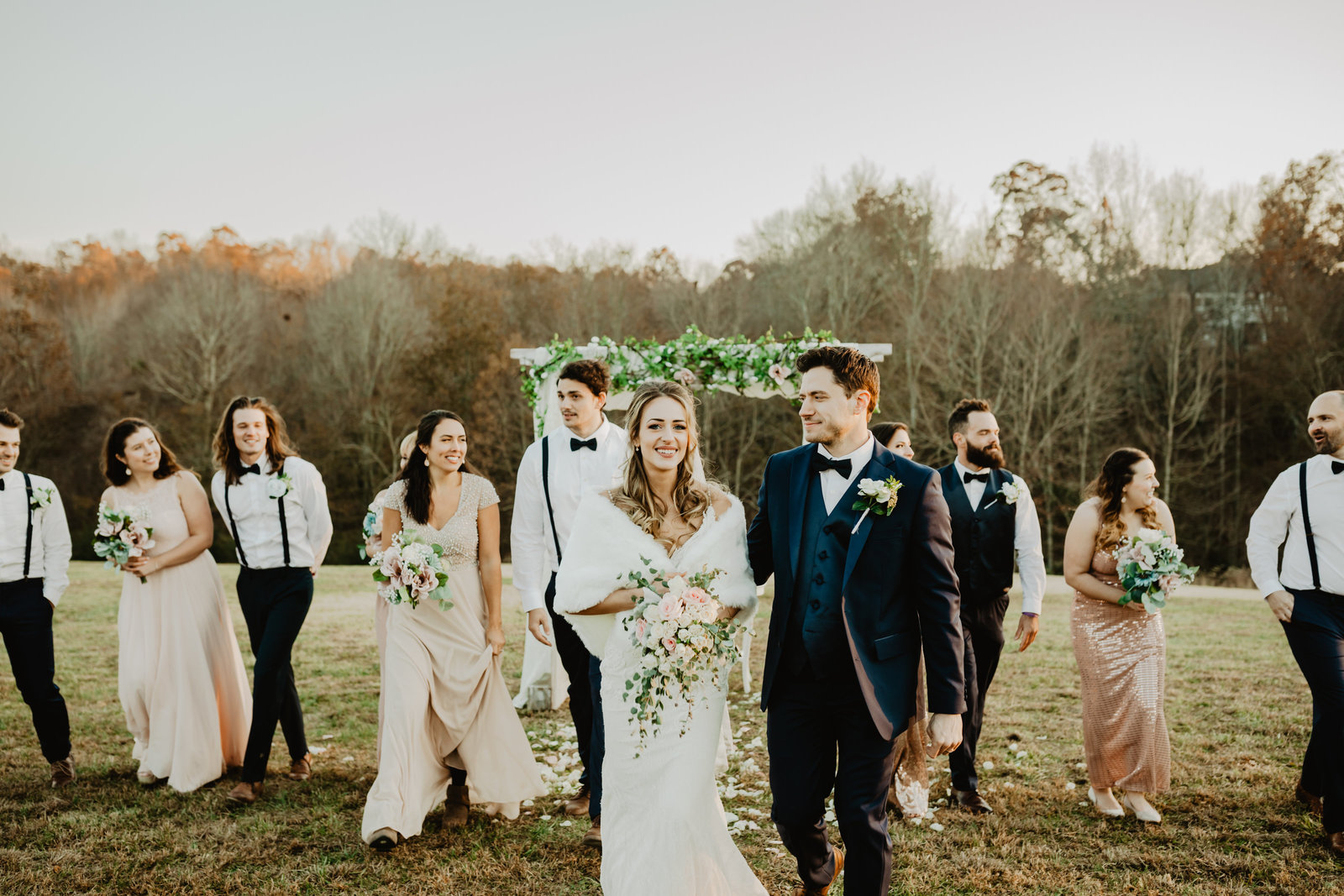 Bride looks at camera while walking with bridal party at Apple Woods Farm