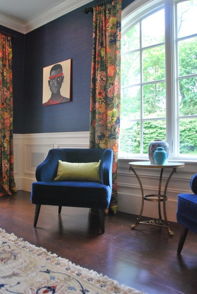 Two blue velvet chairs and an accent table in front of an arched window.