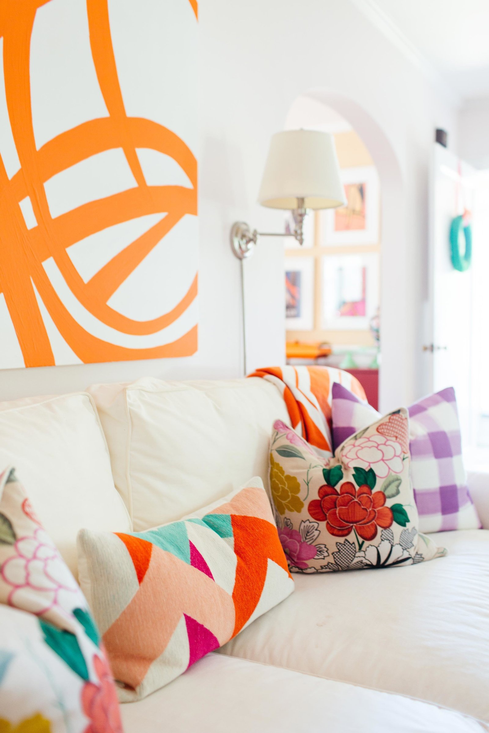 A living room with a large orange and white abstract painting and colorful throw pillows.