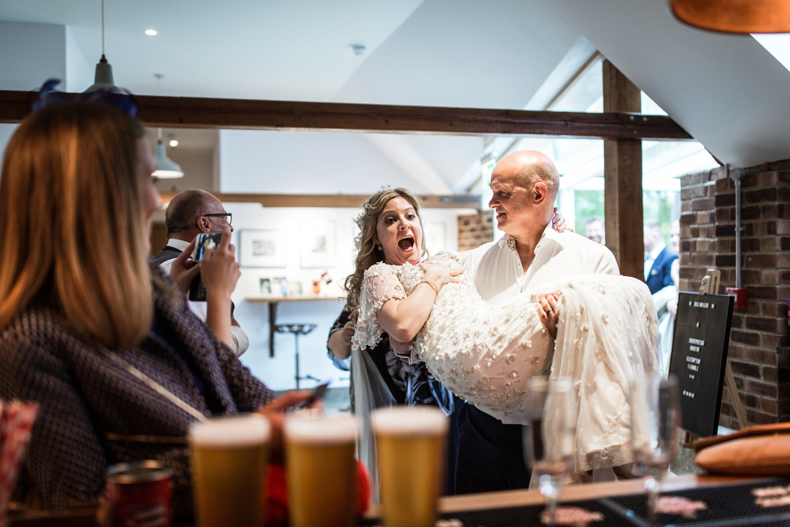 A shocked bride is picked up by her uncle on the way to the bar at a Norfolk wedding venue. The bar is lined with beers and shots.
