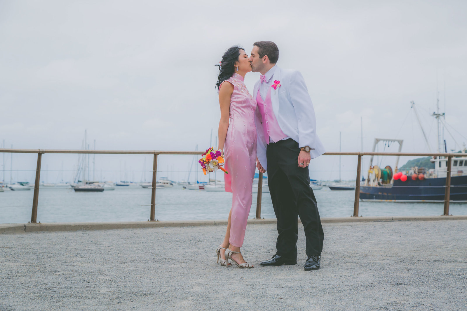 Bride and groom kisses with boats in water at Port Jefferson.