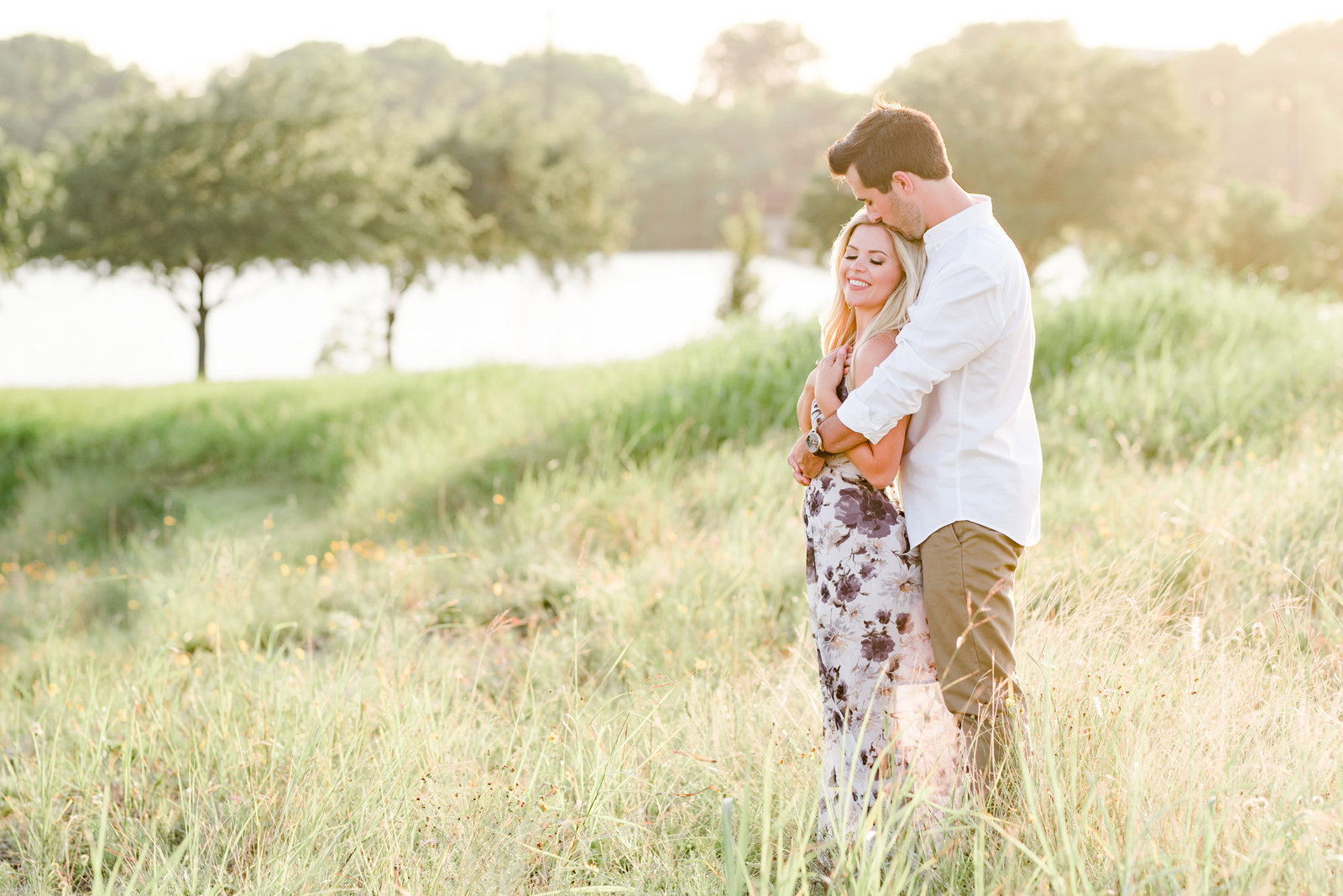 An engaged couple posing in a field at White Rock Lake by Dallas Photographer