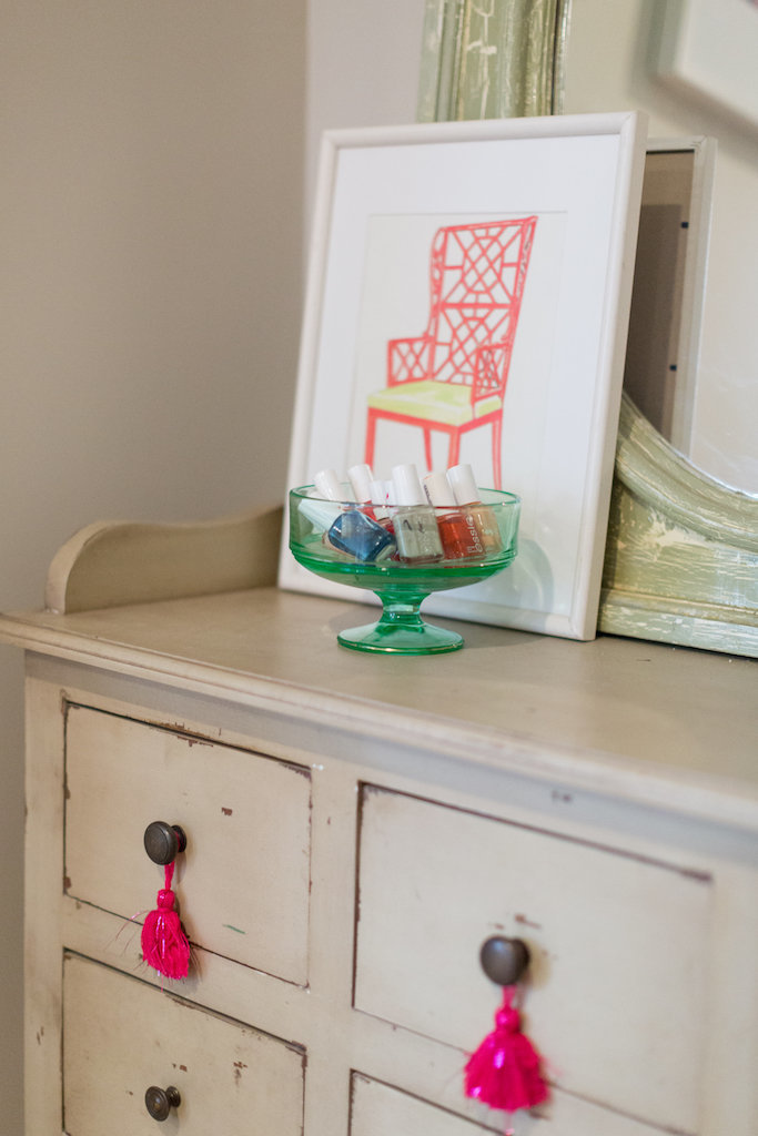 A glass dish and framed art atop a vanity with tassels.