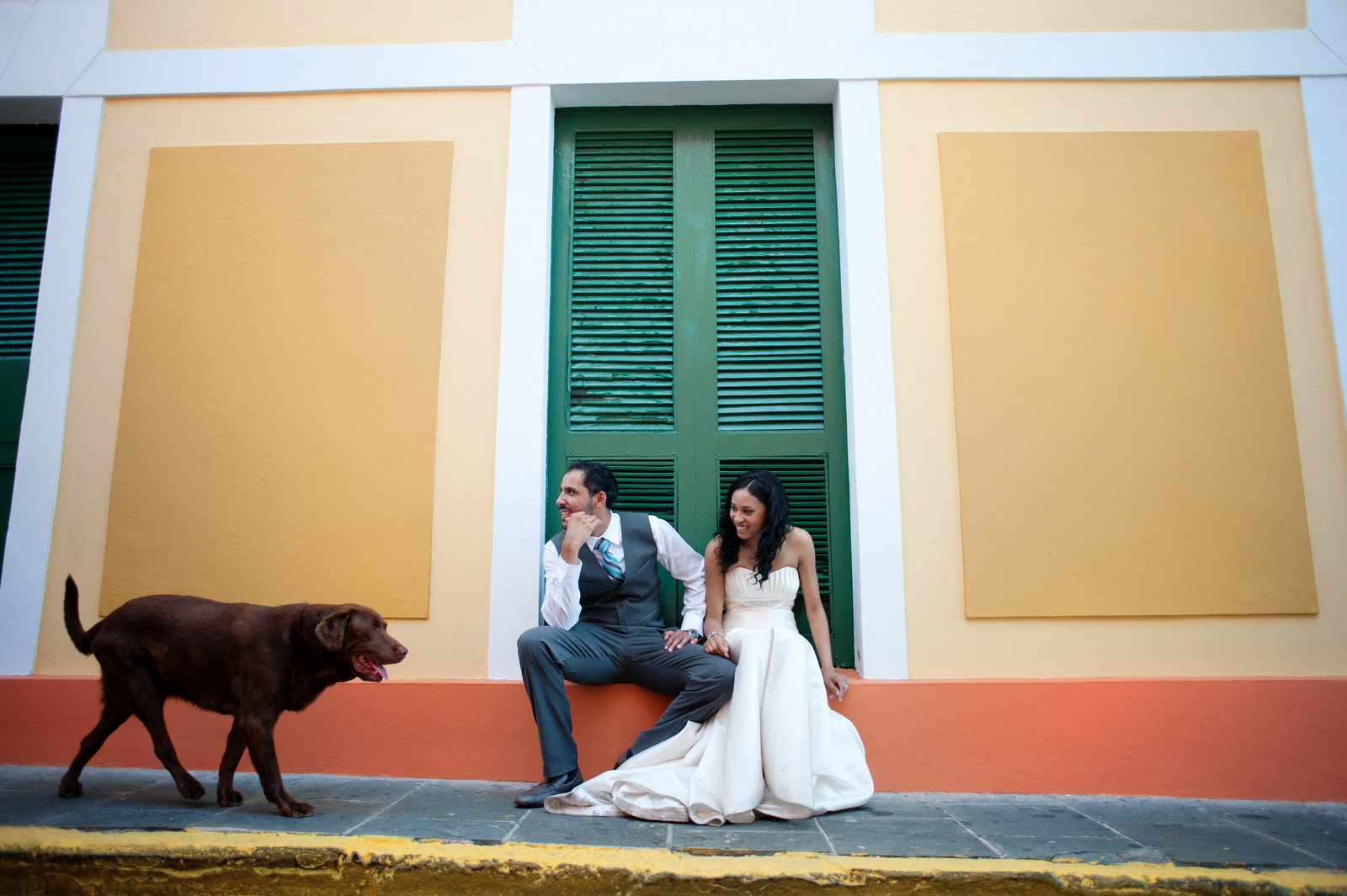couple sit in front of colorful wall in puerto rico as dog walks past