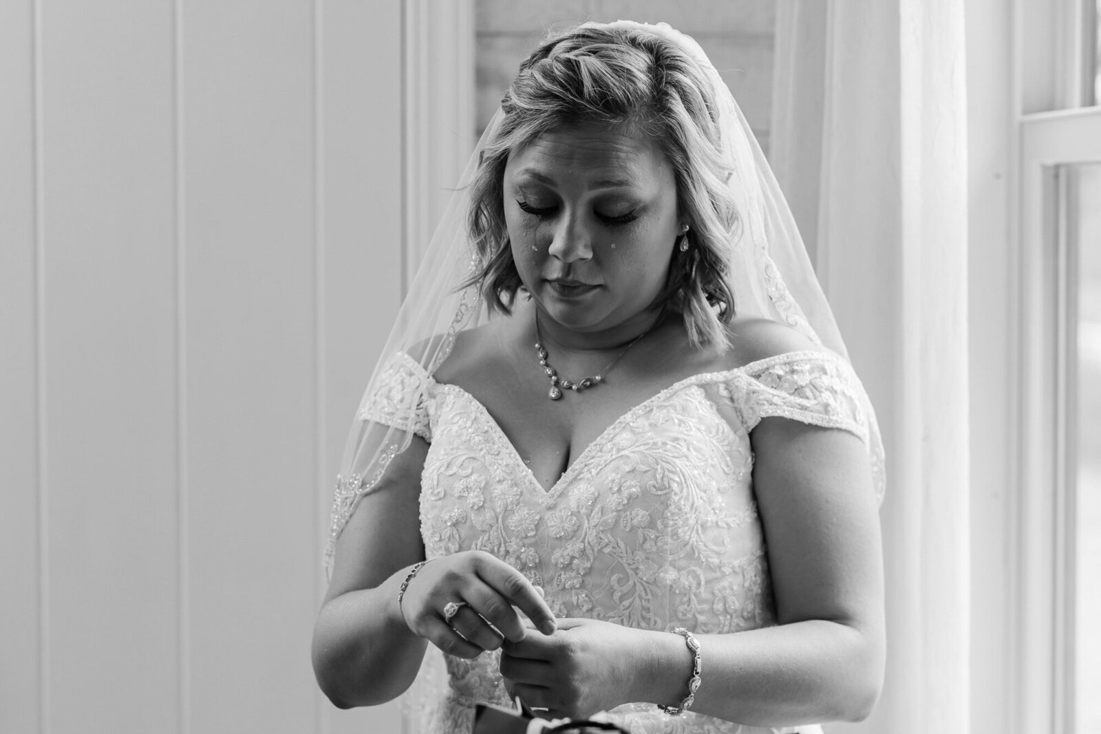Black and white photo of an emotional bride getting dressed for her Kansas City wedding