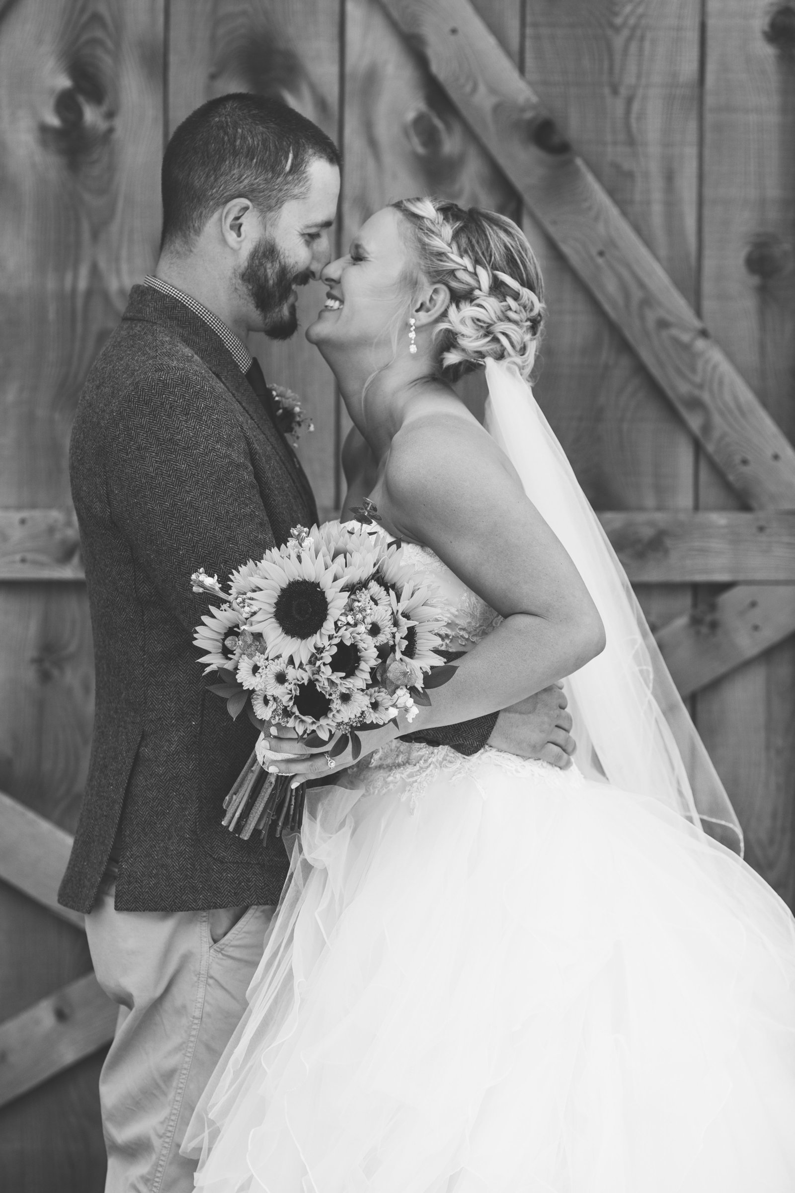 bride and groom  give an eskimo kiss in front of a barn in erie