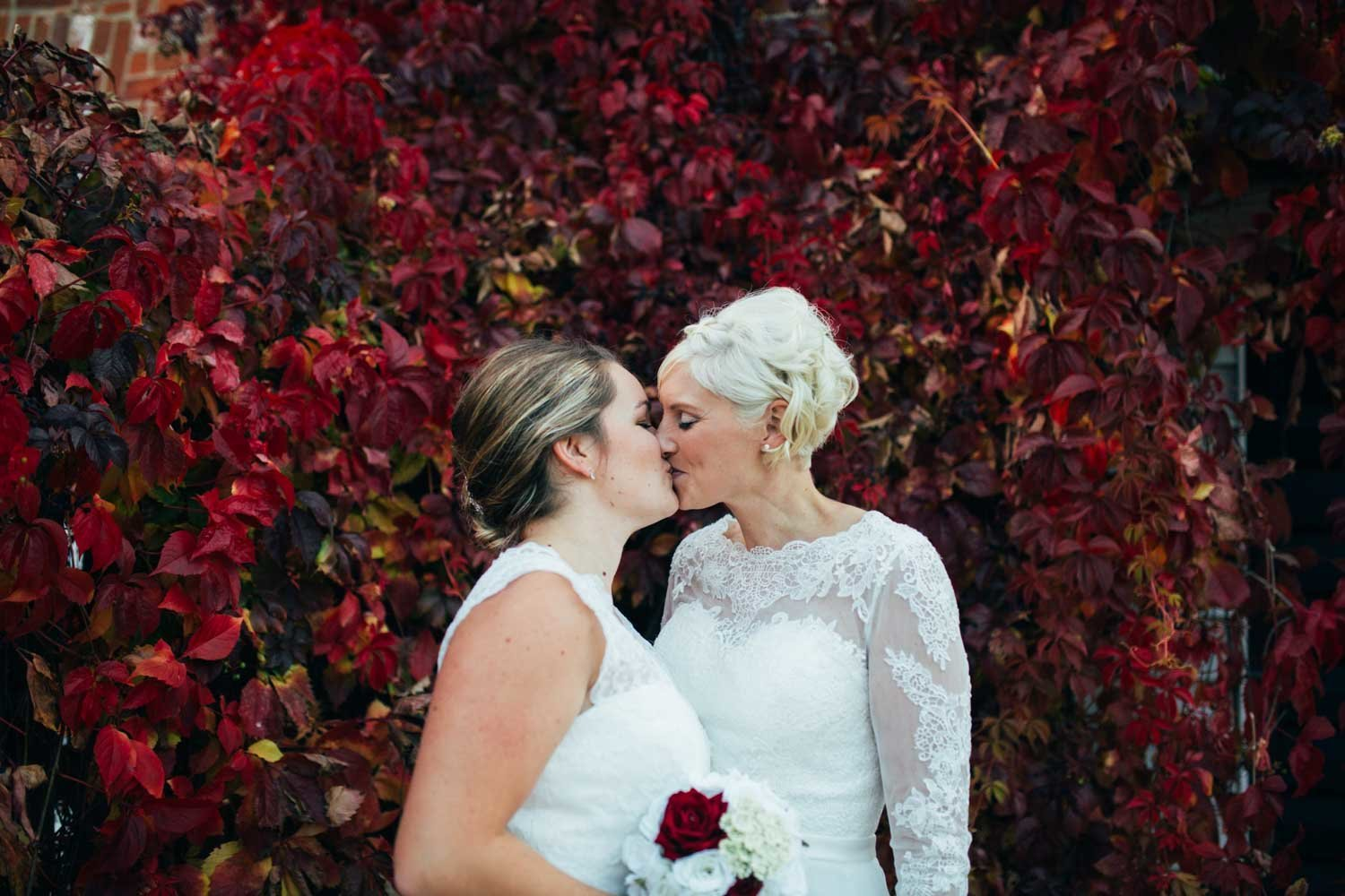 Same sex lesbian couple kissing against red autumnal leafy backdrop at their wedding at The Venue at Kersey Mill in Suffolk
