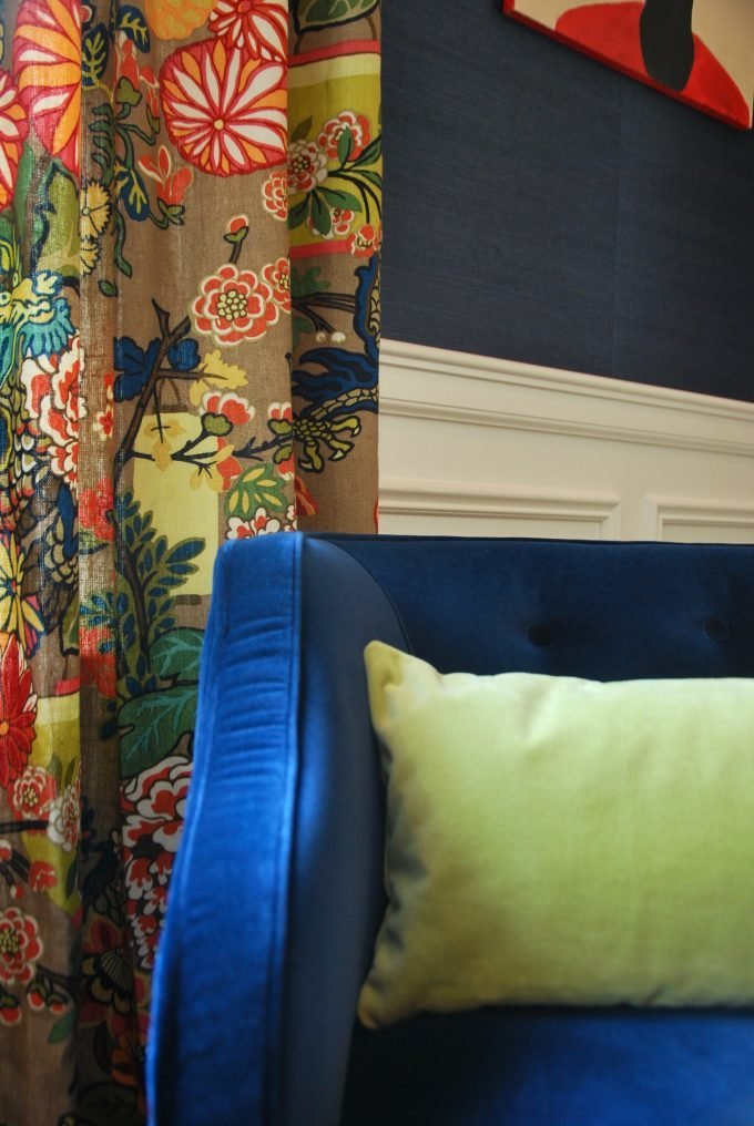 A blue velvet chair with lime green throw pillow in front of floral drapes.