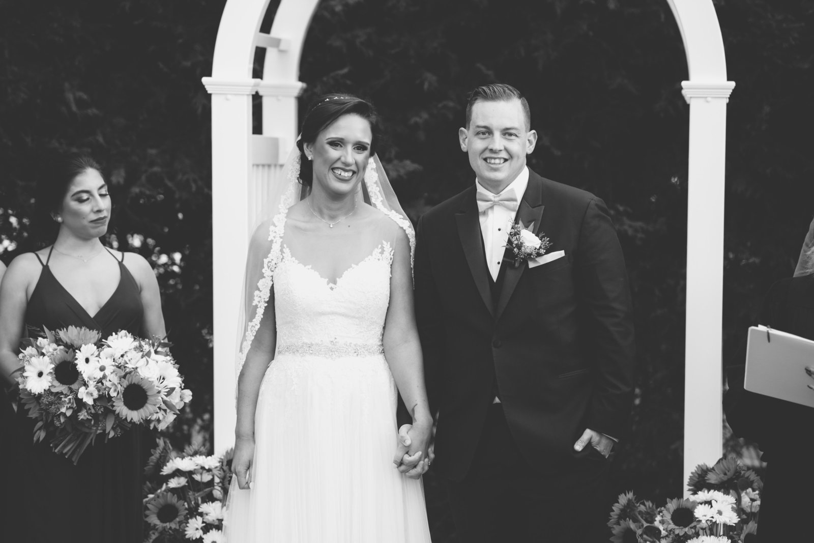 black and white photo of bride and groom walking down the aisle after ceremony  from Three Village Inn wedding