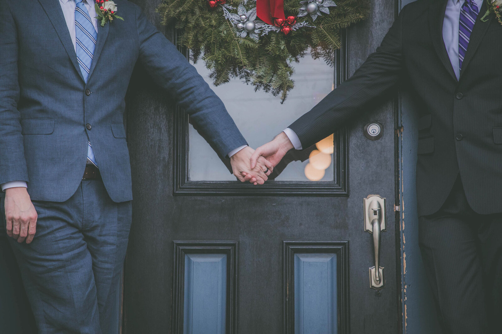 Two grooms hold hands by door.