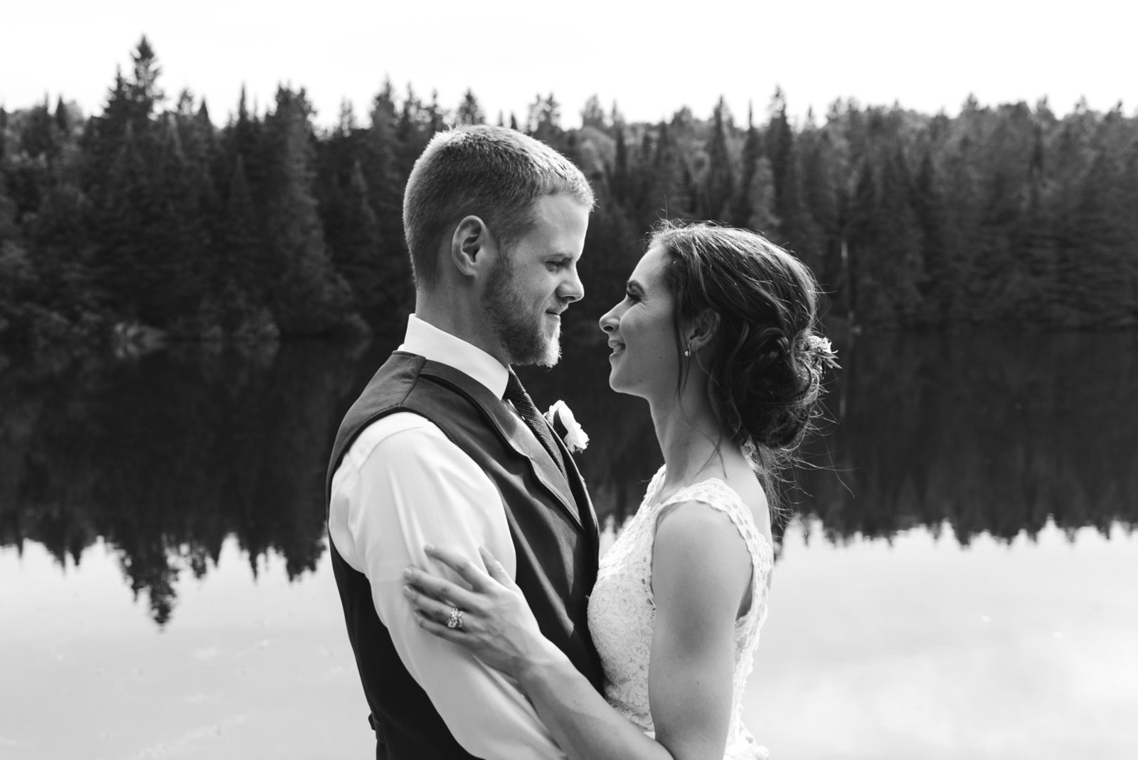 bride and groom smiling at each other by the lake