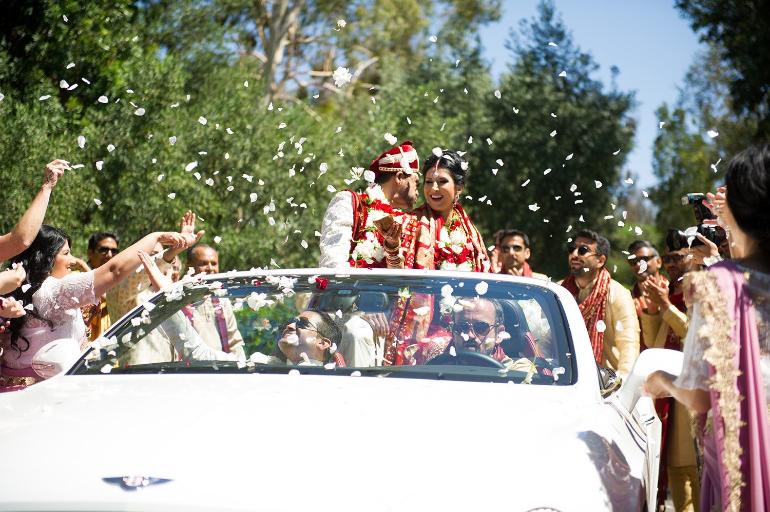 Bride and groom are showered with flower petals and rice after their Hindu wedding ceremony