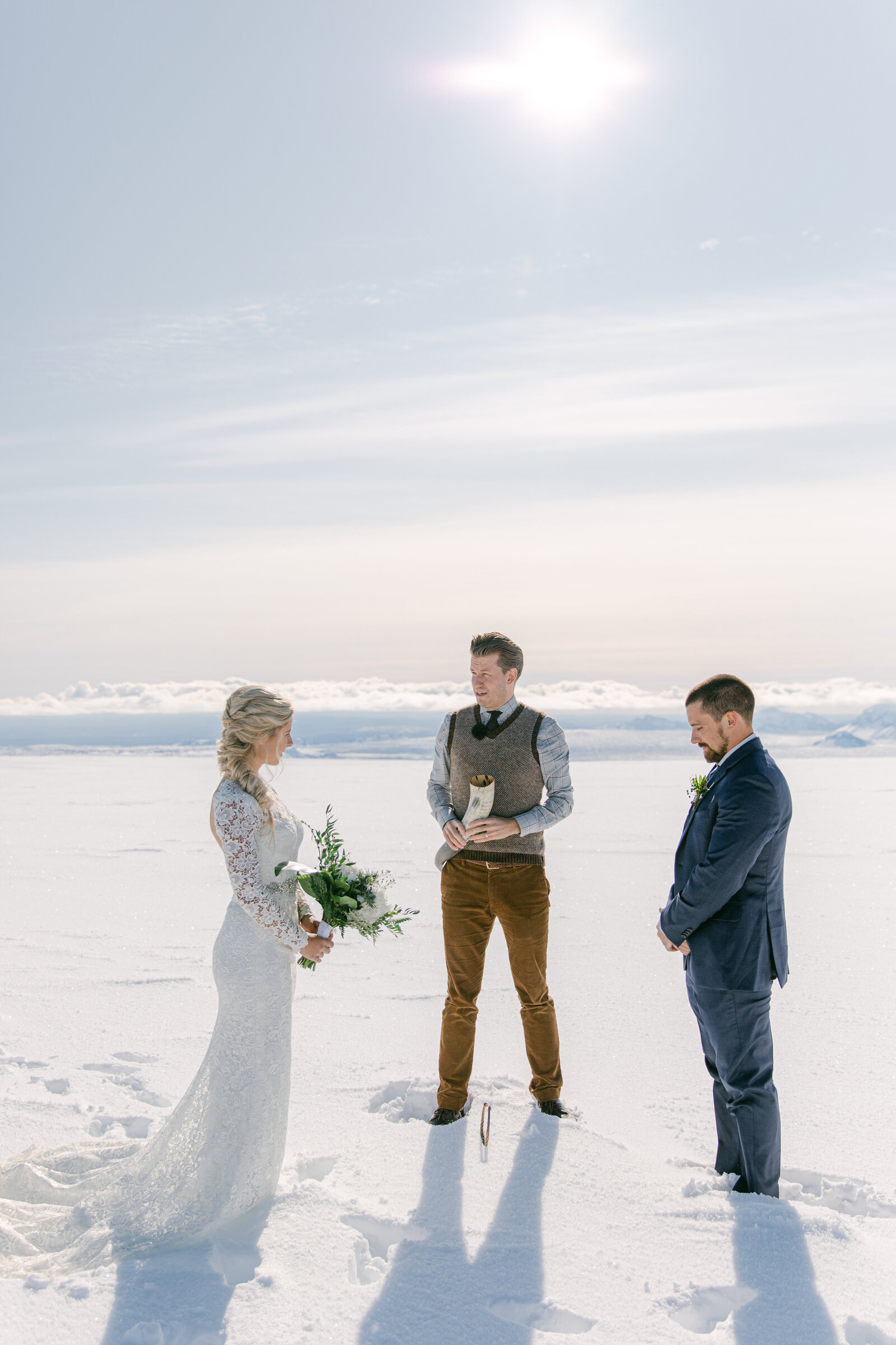 bride and groom and wedding officiant on top of a glacier in iceland exchanging vows