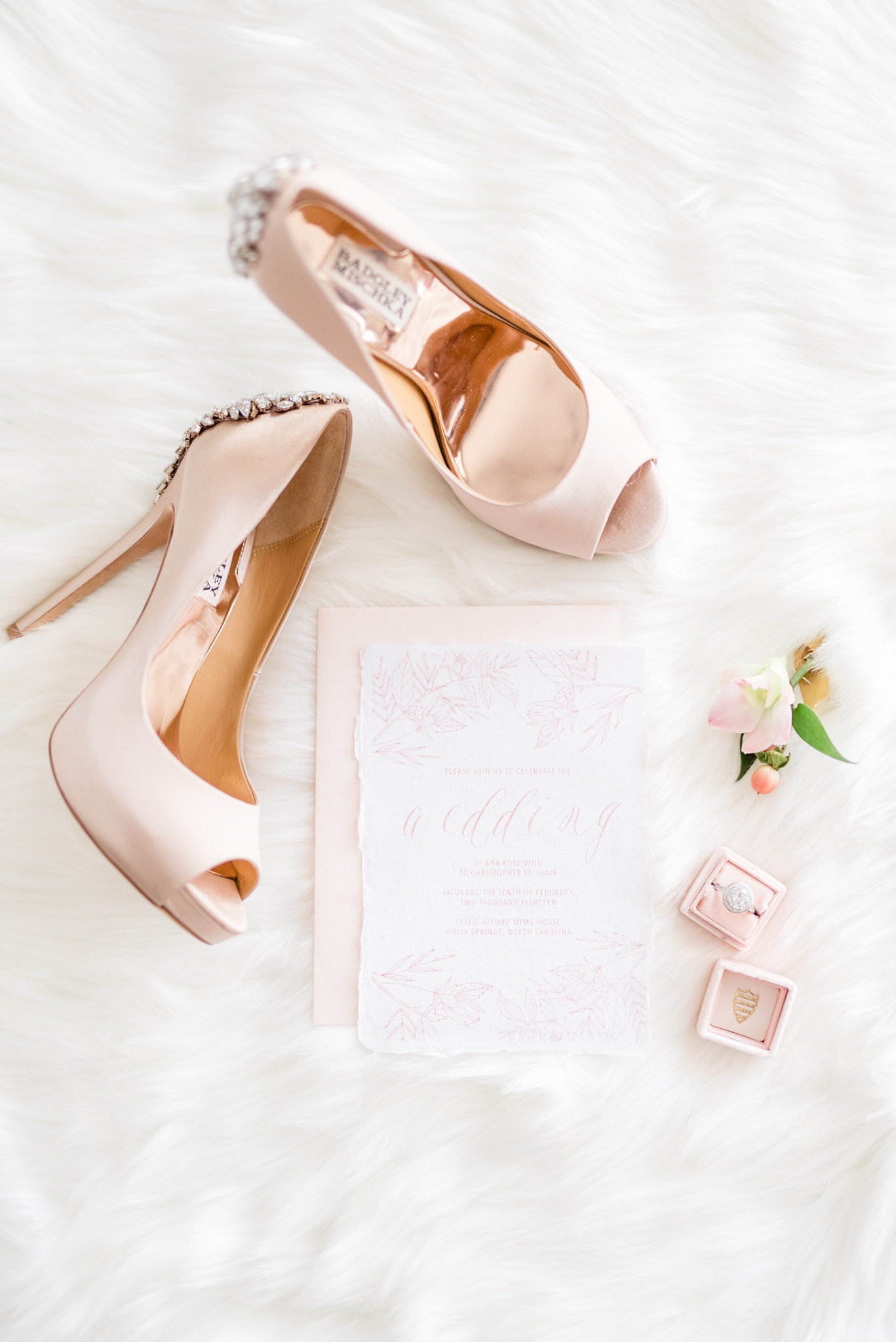 Wedding shoes sit next to invitation suite.