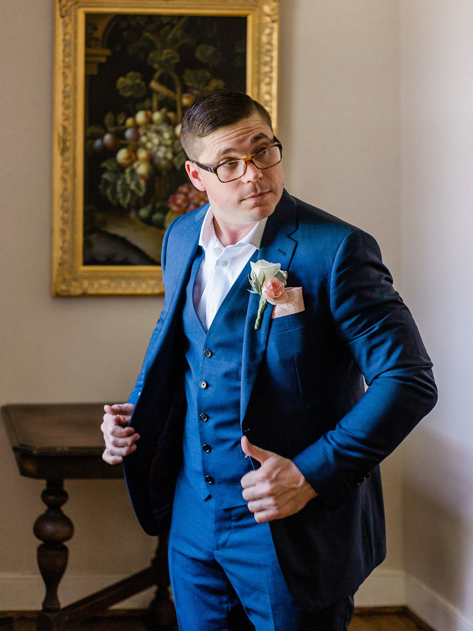 Groom in navy three piece suit looks off to the side as he gets ready in a manor style home