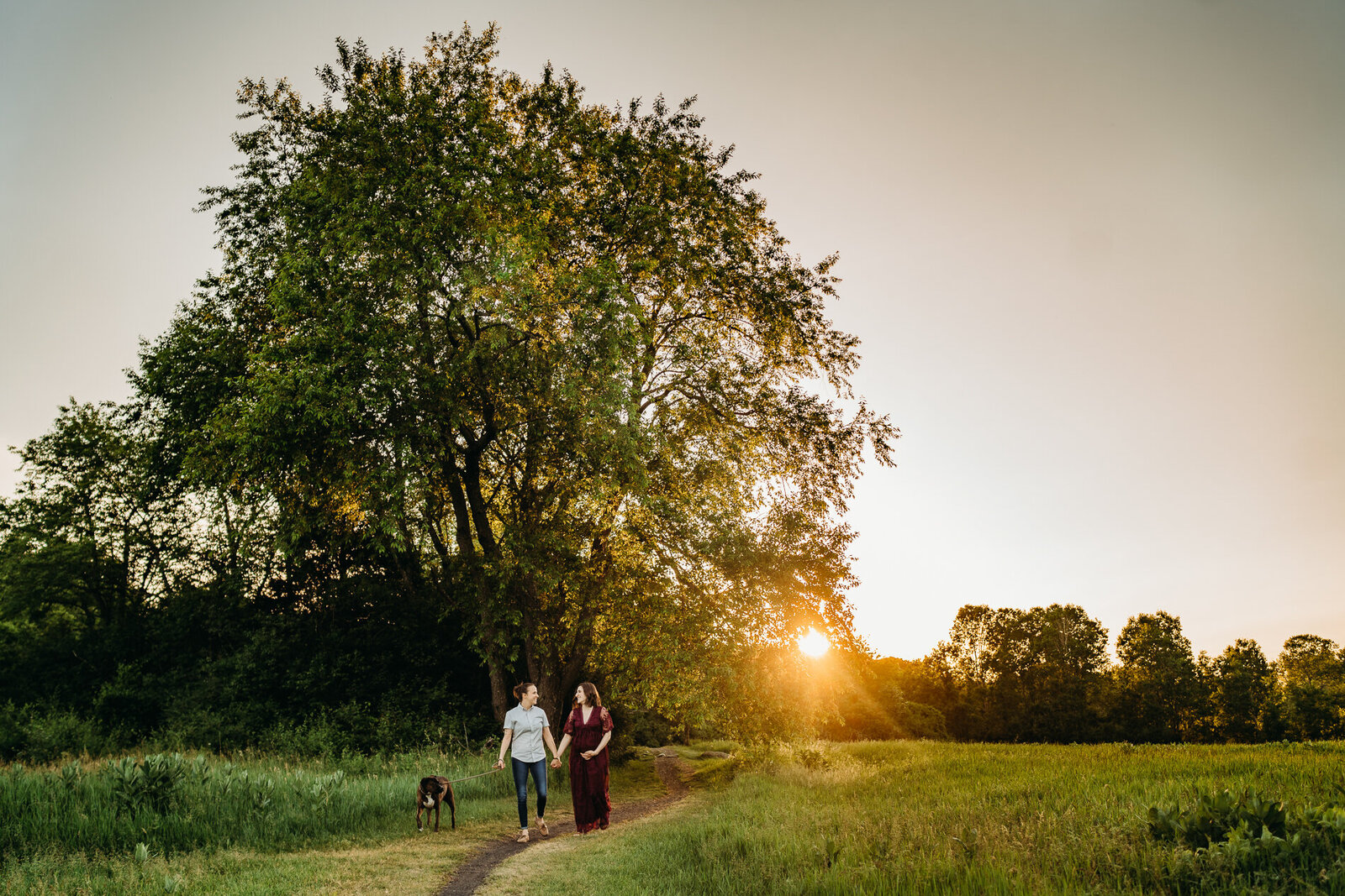 landscape photo of pregnant couple walking at sunset