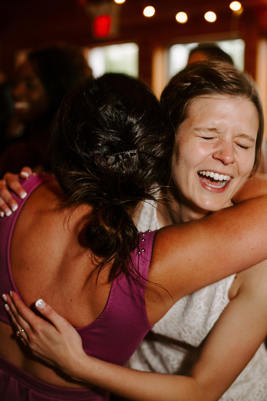Bride hugging her bridesmaid on hr Minneapolis wedding day