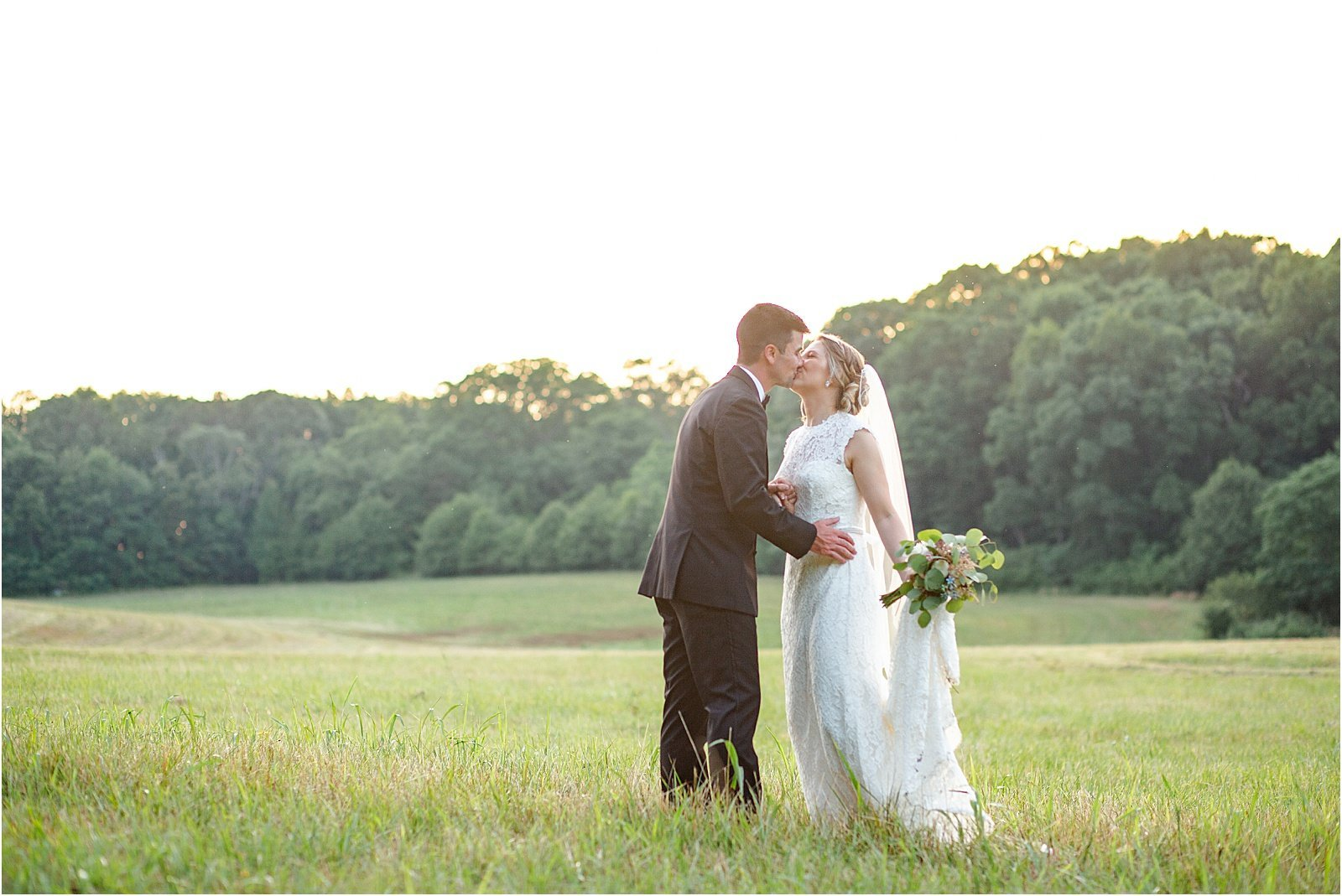 Wedding photography couple in Greenville, SC kissing in a field with a sunset