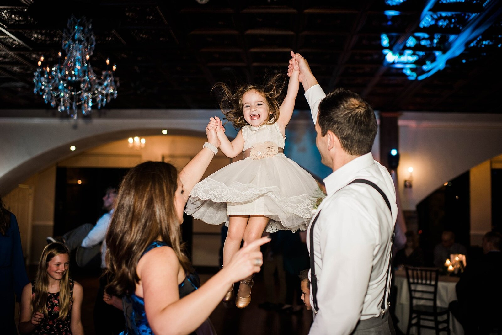 Wedding guests hold their daughter in the air at the pavilion event space