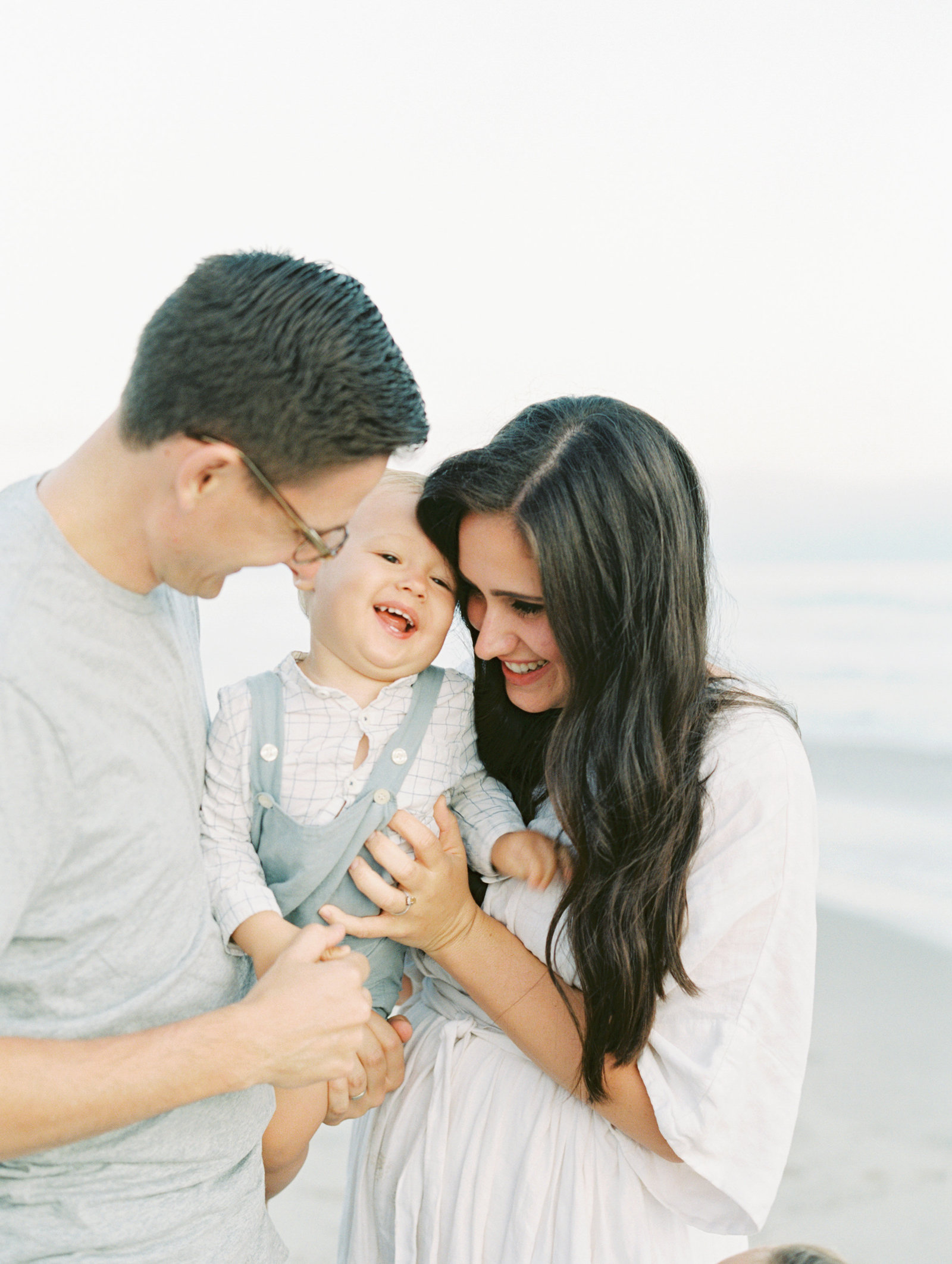 little boy laughing, being held by his mom and dad, they are looking at him and smiling, on the beach