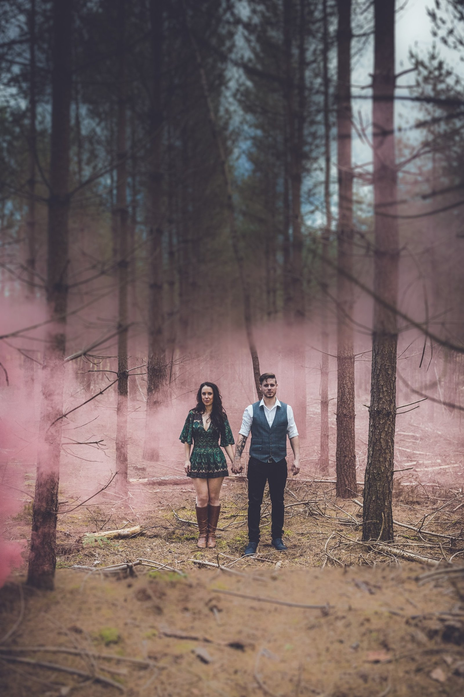 A couple stand facing the camera and hold hands at Bacton Forest, Norfolk. A pink smoke bomb gives a surreal atmosphere