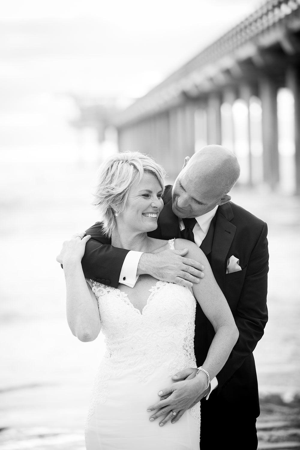 black and white bride and groom with pier