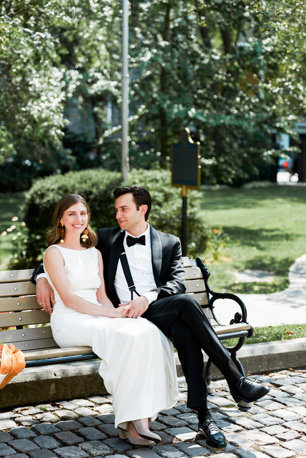 Modern couple sit on a bench at Osgoode Hall for their wedding photos