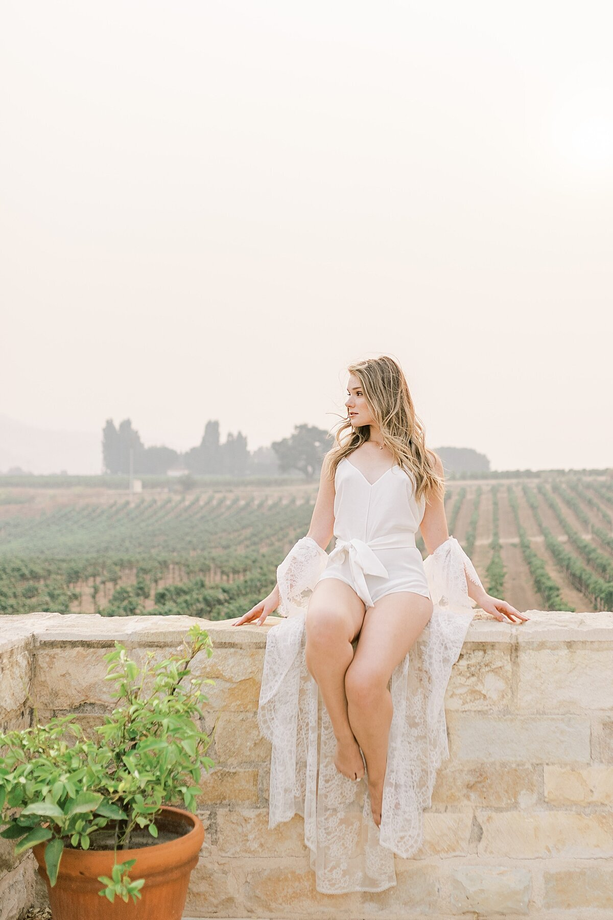Bride lounging in Bridal lingeire surrounded by vineyards