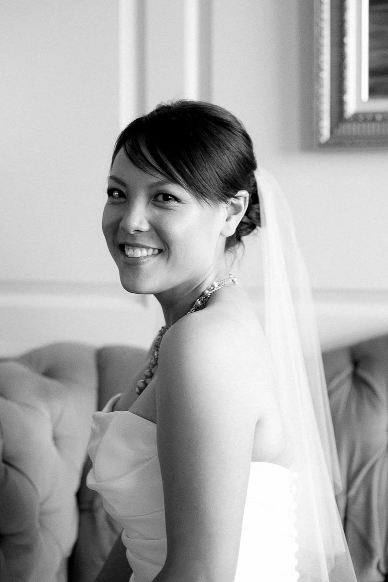 Bride sits on couch, Hotel DuPont, Wilmington, Delaware. Kate Timbers Photography.