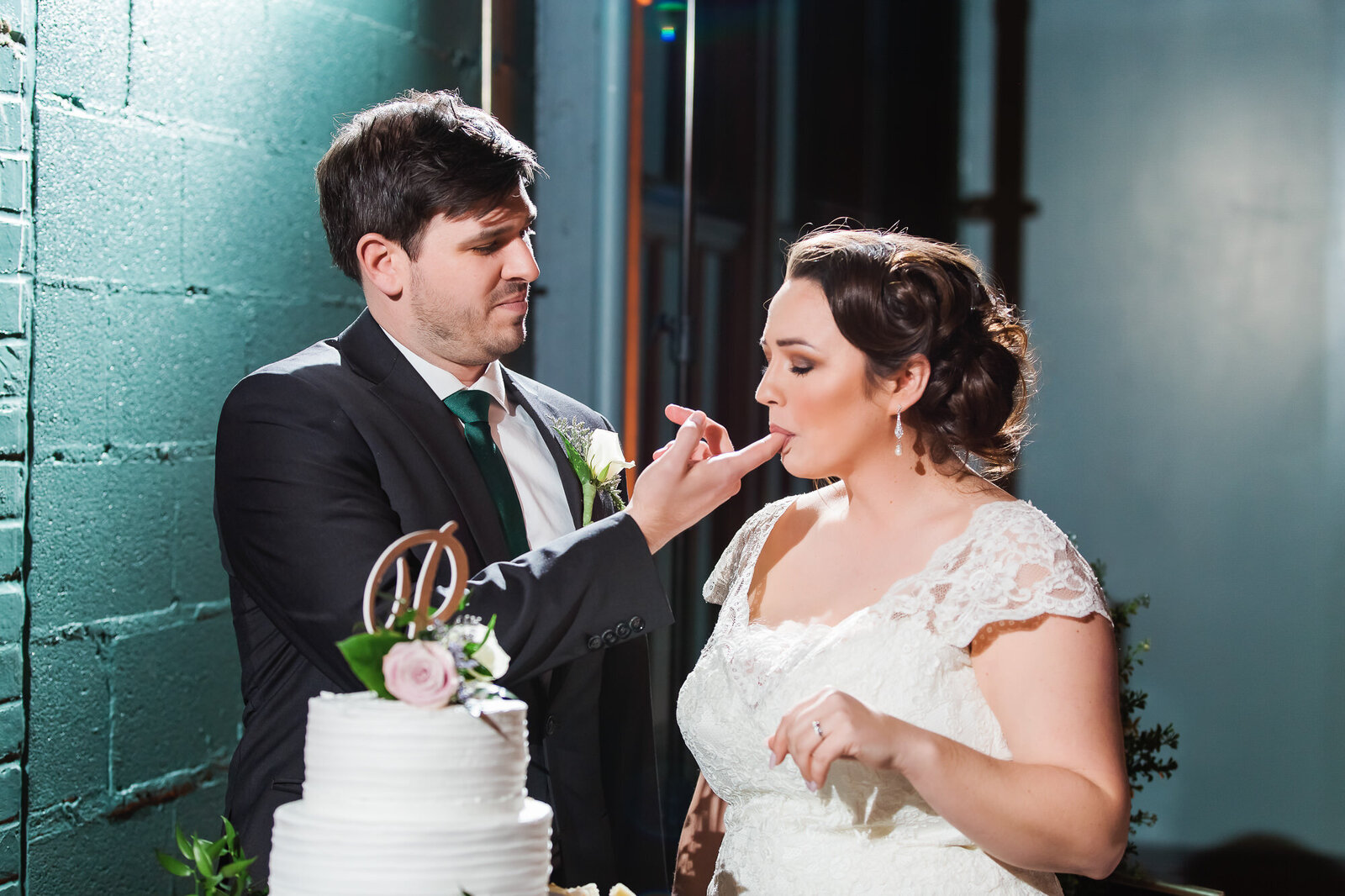 Bride licking cake off her groom's finger at their NEO on Locust wedding reception in St. Louis