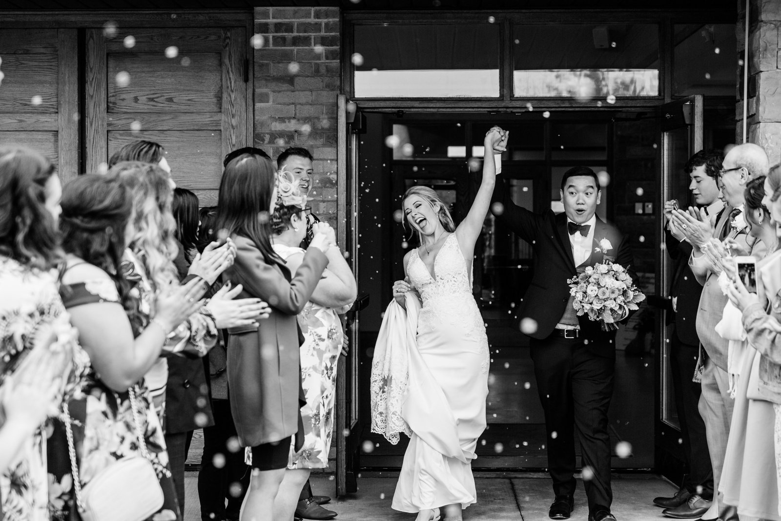 Newly-married-couple-celebrates-their-marriage-as-they-exit-their-ceremony-with-friends-and-family-cheering-and-blowing-bubbles
