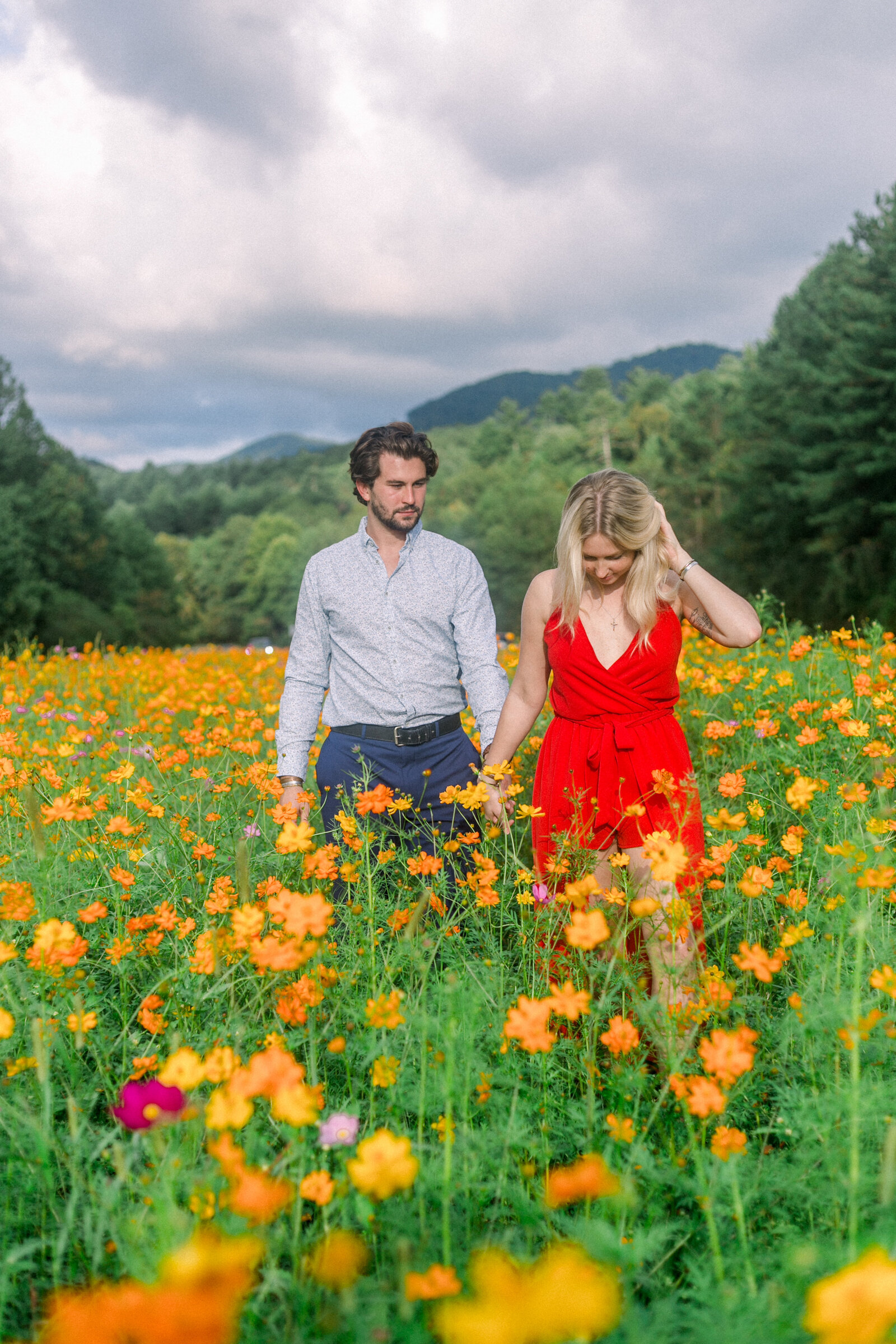 Couple walking through a field of wild flowers captured by Staci Addison Photography