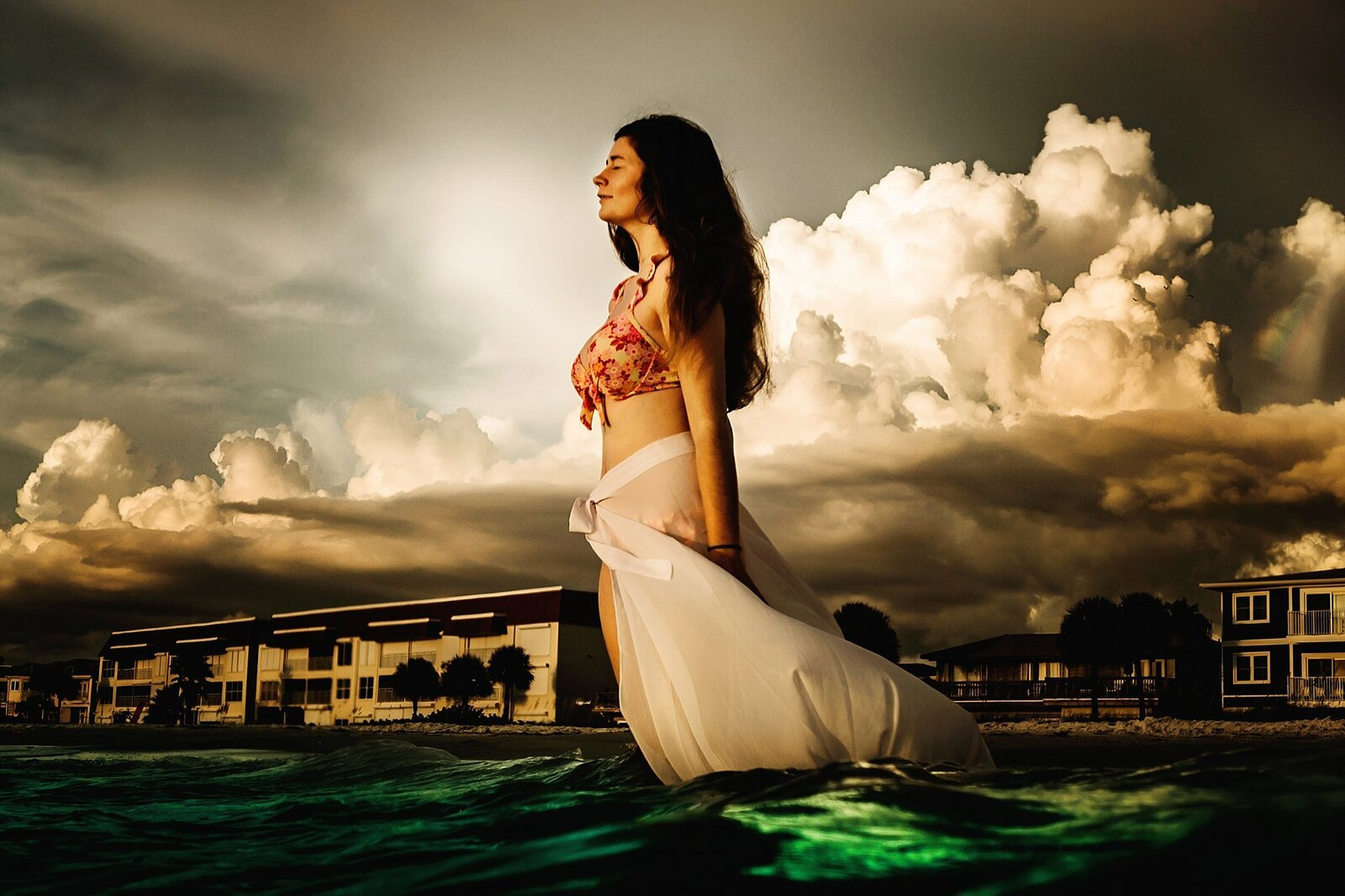 girl standing in water with storm clouds