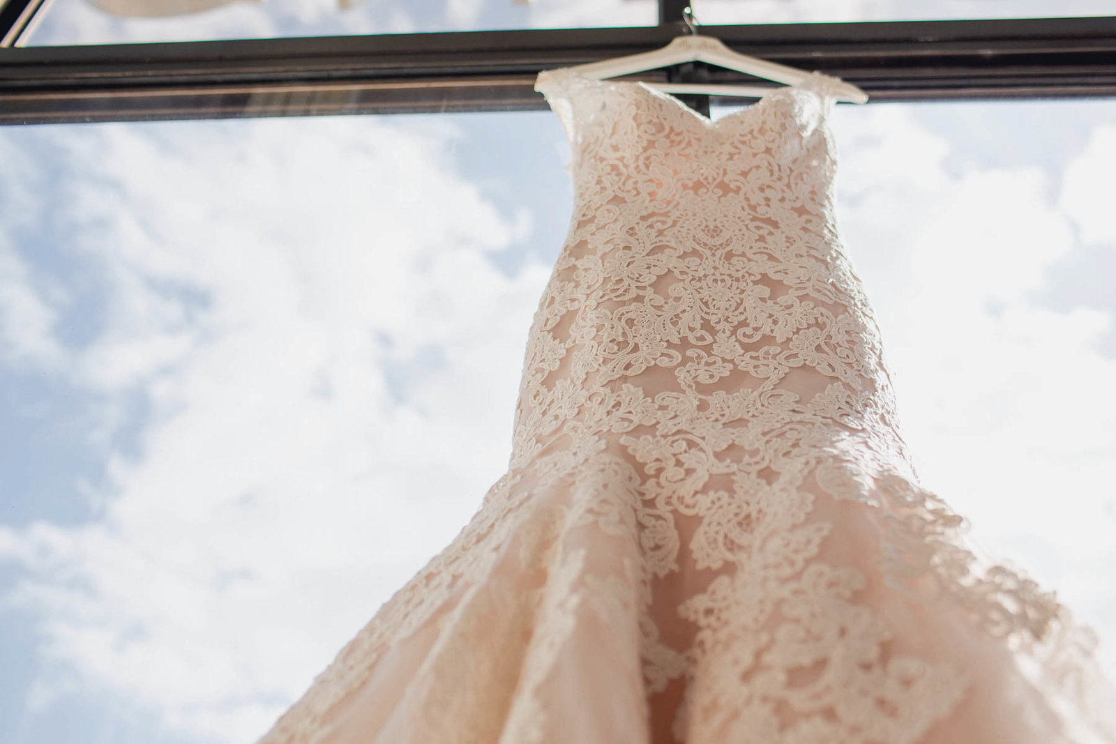 Dress hangs in window overlooking the water and boatyard, Destination wedding, Hyatt Regency, Sarasota, Florida