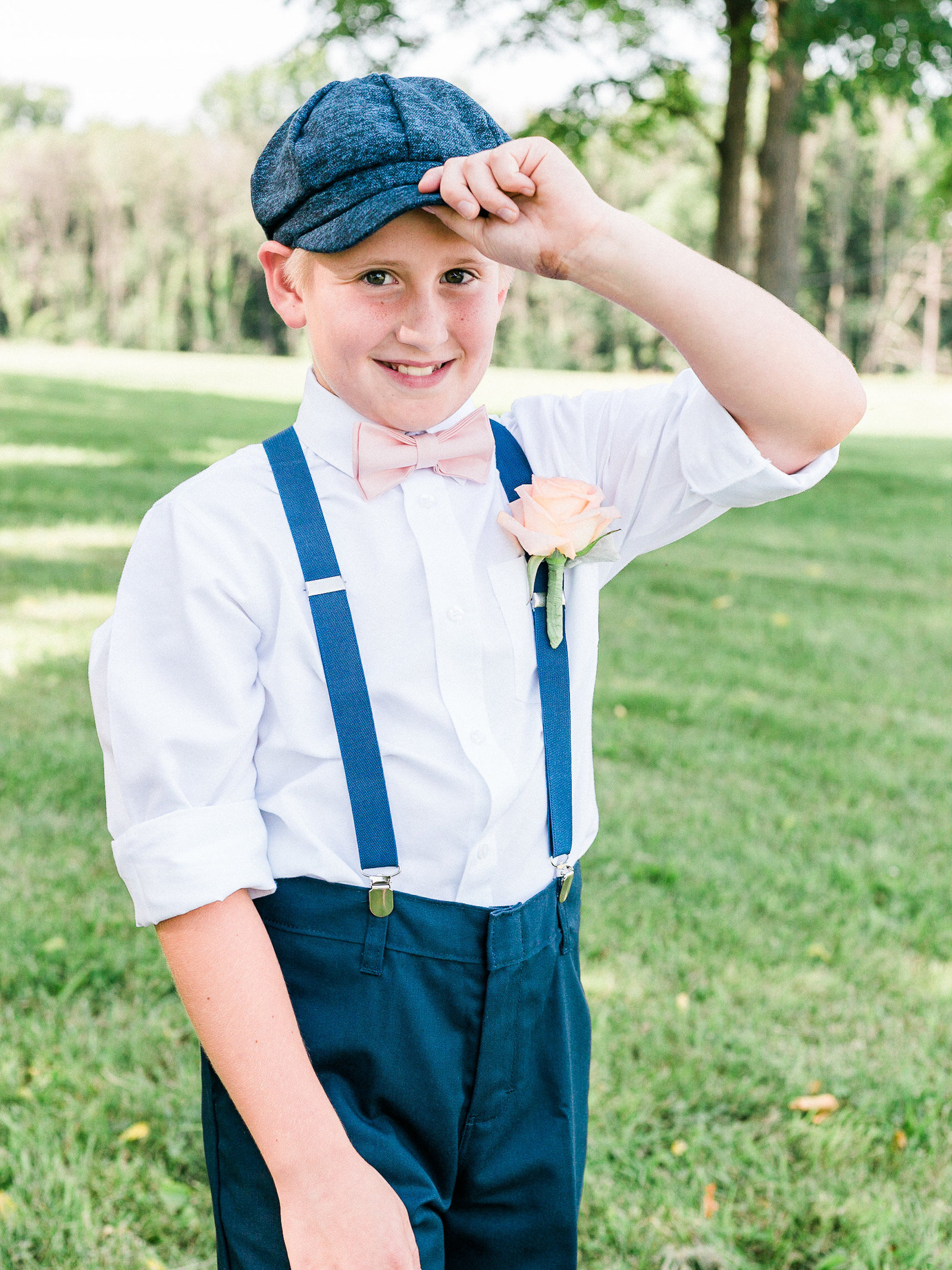 Page boy style ring bearer in flat cap and suspenders