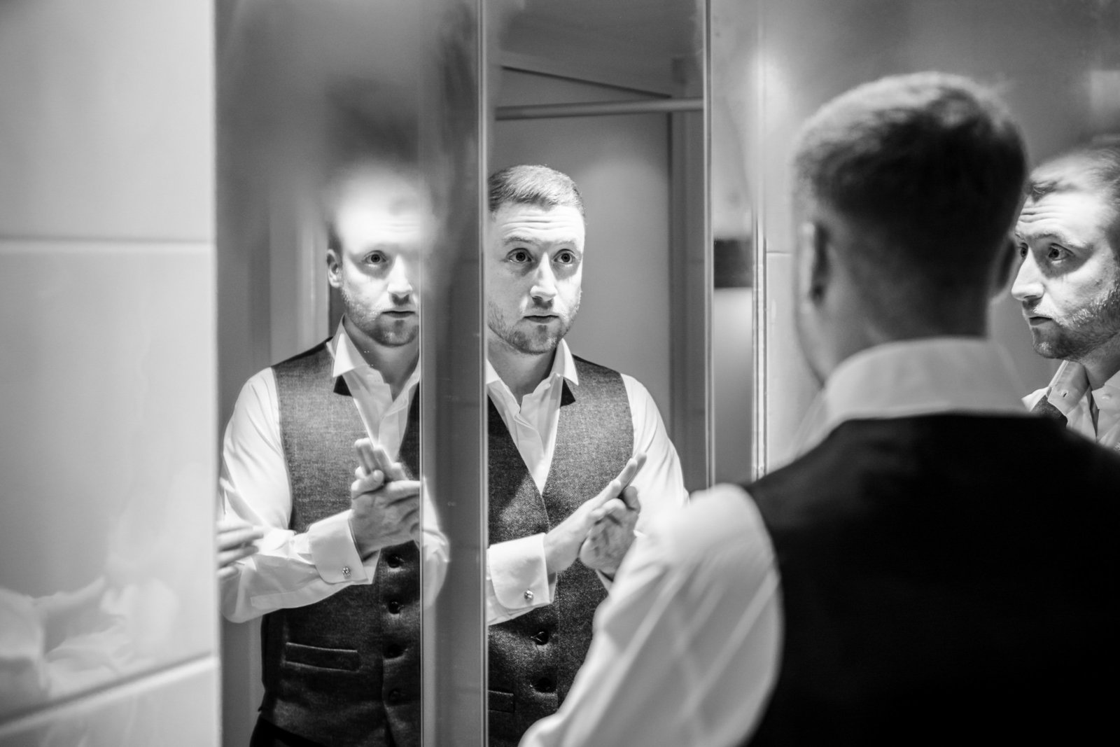 A groom prepares for his wedding day in front of multiple mirrors in a bathroom in Norfolk.