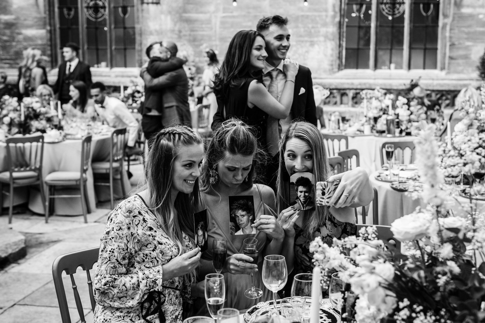 Wedding guests laugh at photo of the groom as a young man while guests hug and laugh in the background at Hengrave hall.