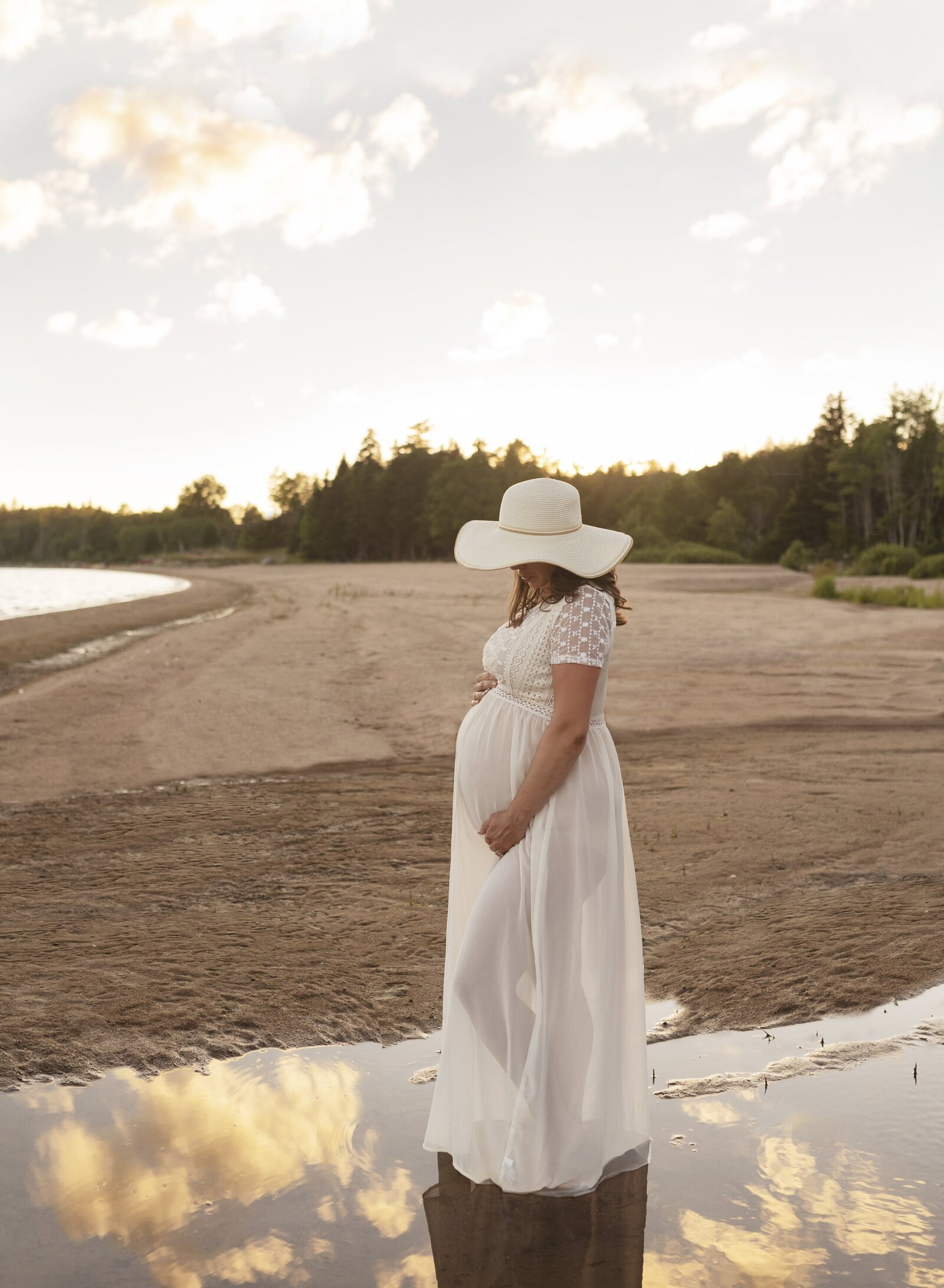 summer maternity pictures at a beach with a woman wearing a large hat