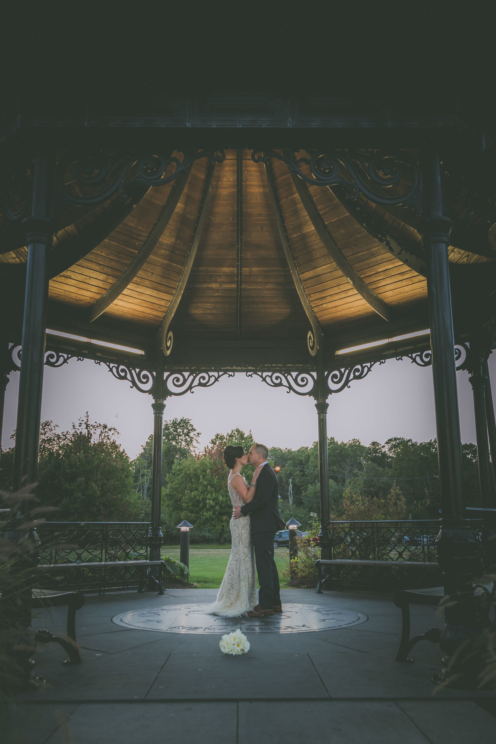 Bride and groom kiss under a gazebo in New Jersey.