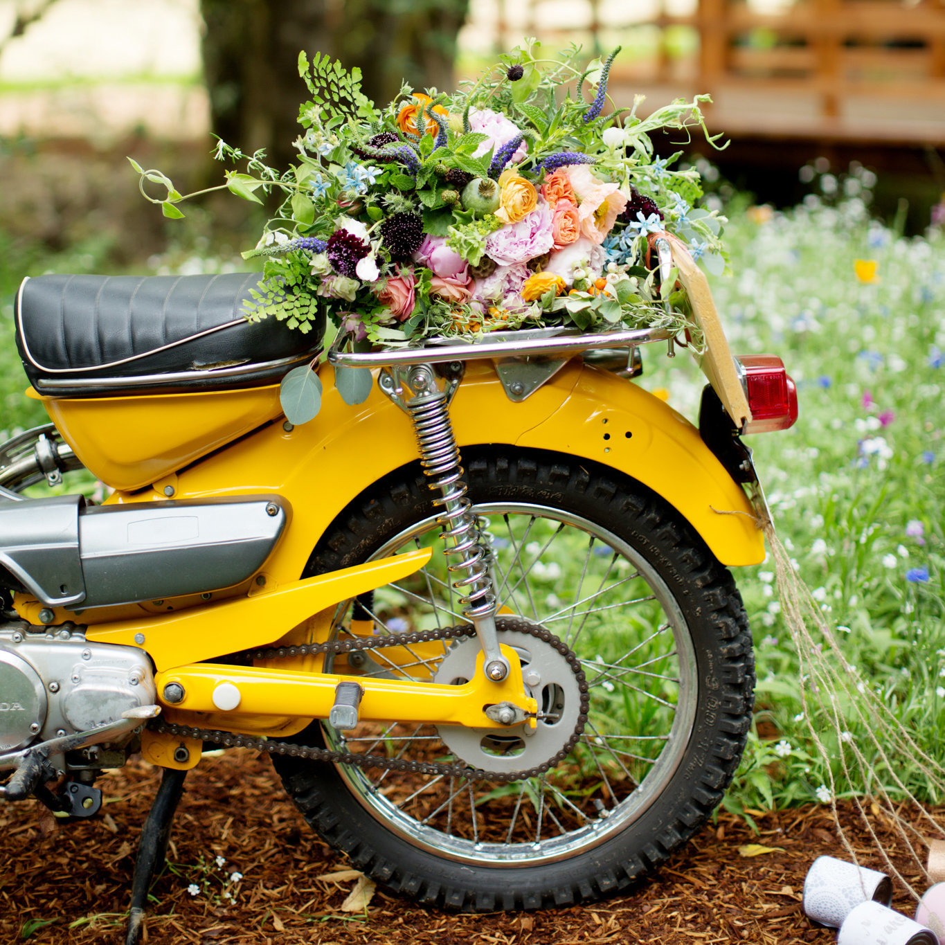 a pretty wildflower bouquet sits atop a bright yellow motorcycle that has just married cans tied to the back