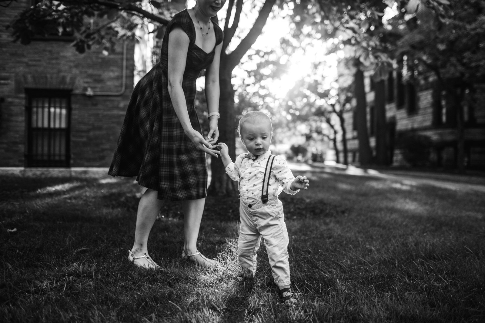 woman holds hand of toddler boy learning to walk in cambridge ma
