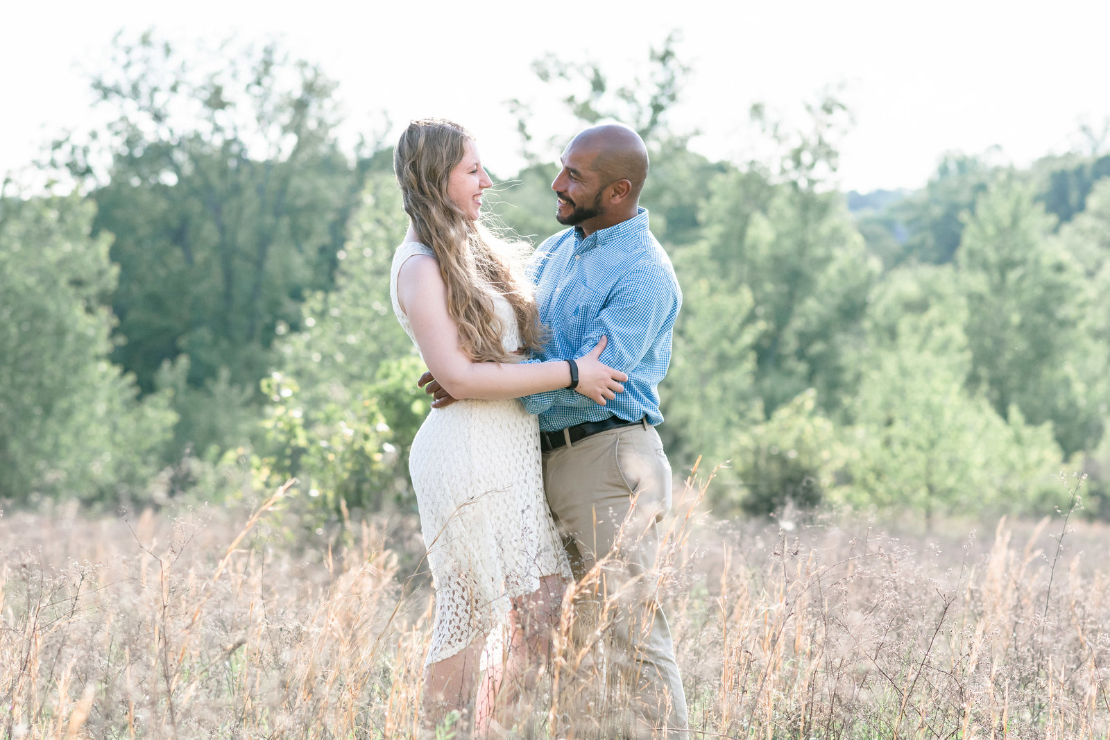 Charlotte engagement photographer shot of couple in field in uptown charlotte